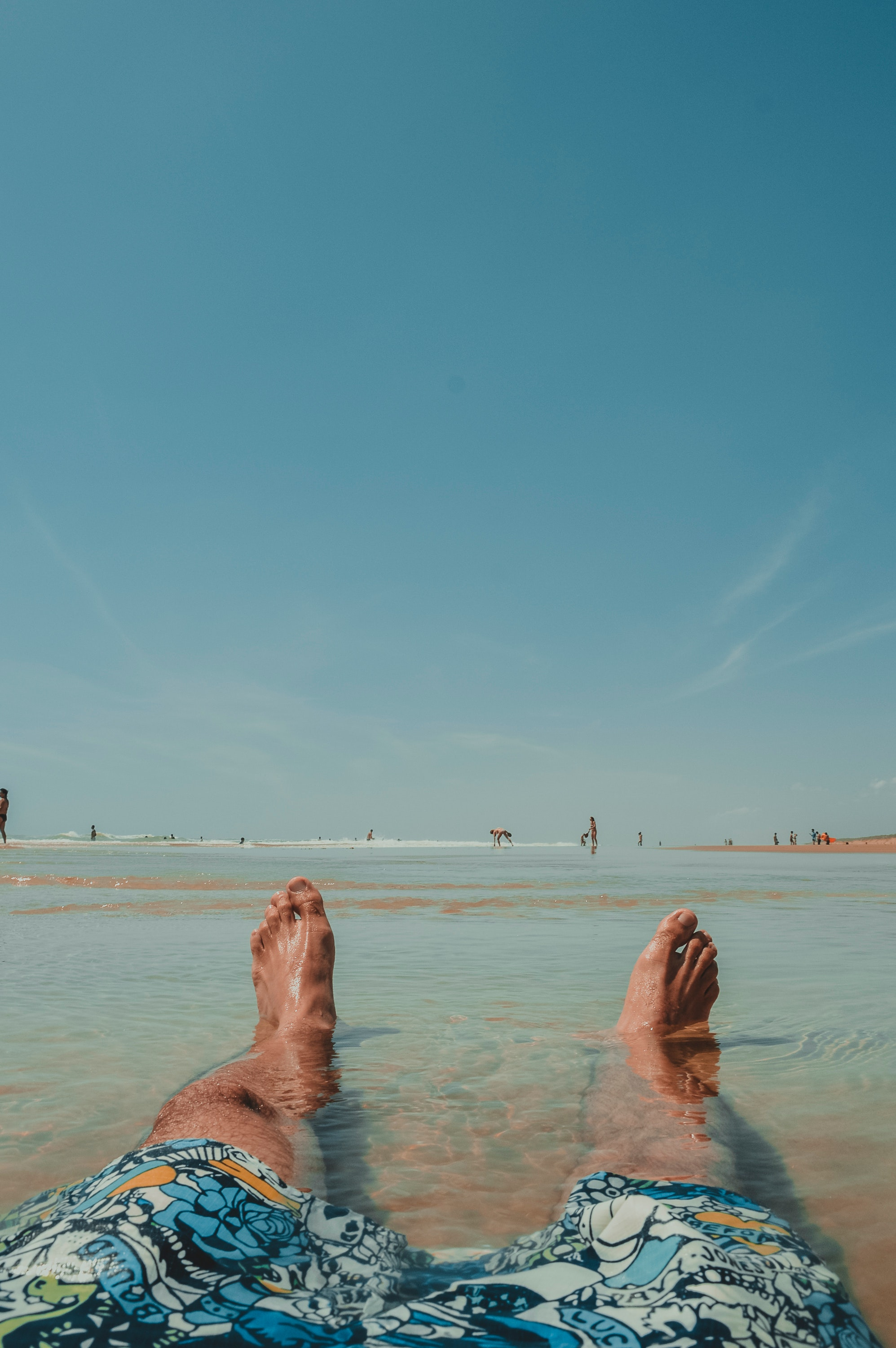 Person Wearing Doodled Boardshorts Sitting on Surface With Water, Beach, Relaxation, Wet, Water, HQ Photo