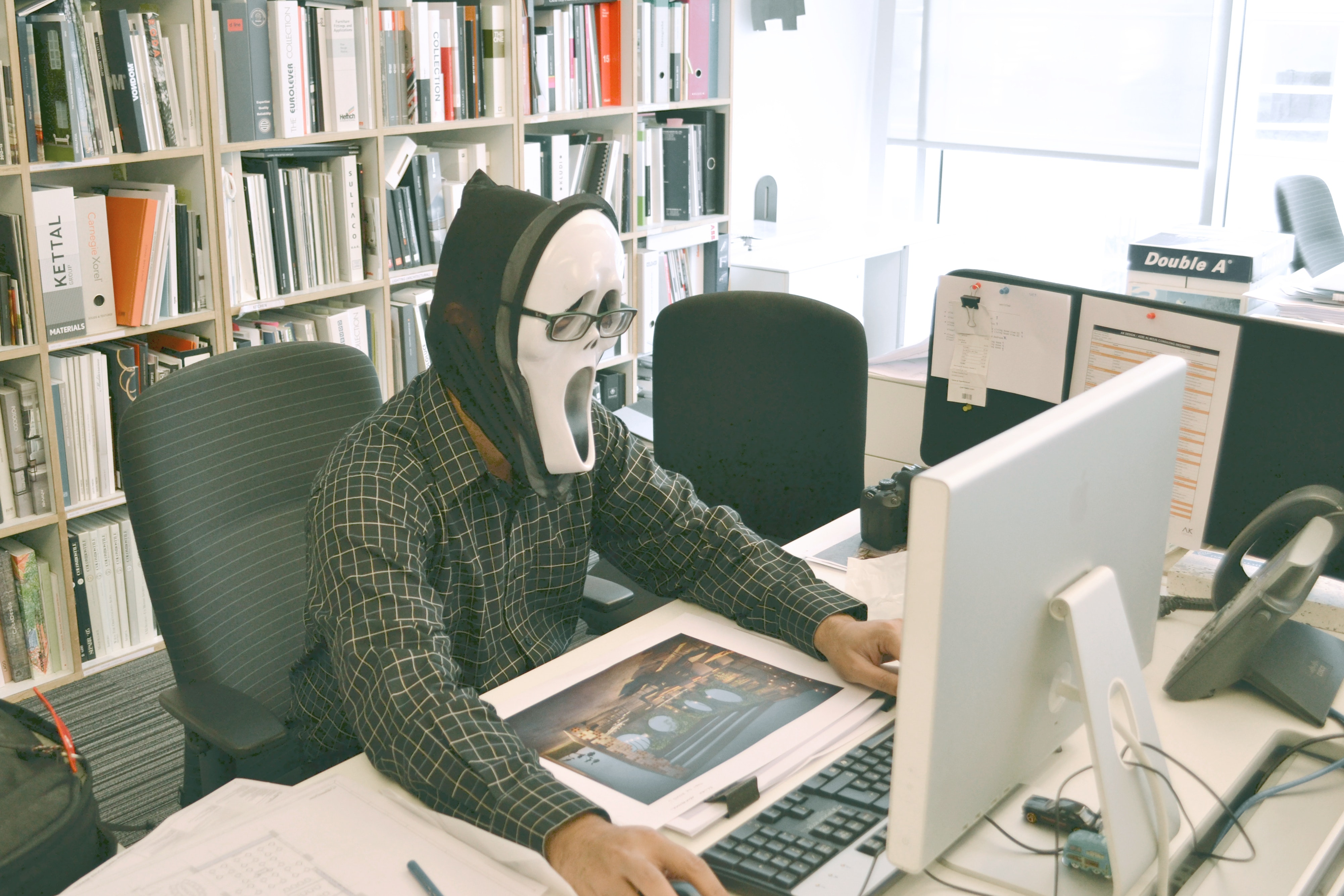 Person wearing scream mask and black dress shirt while facing computer table during daytime photo