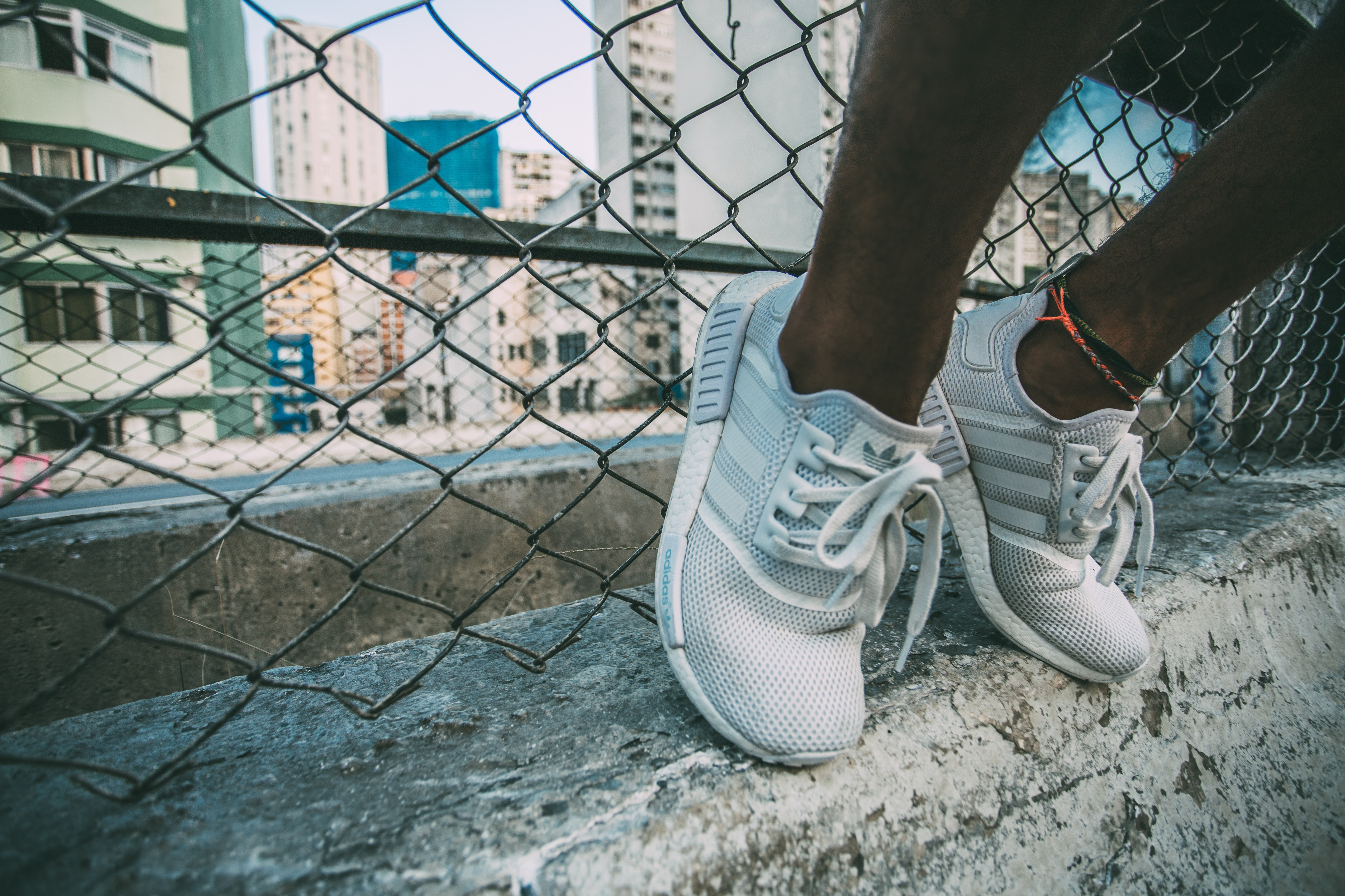 Person wearing white adidas low top shoe near gray cyclone fence photo