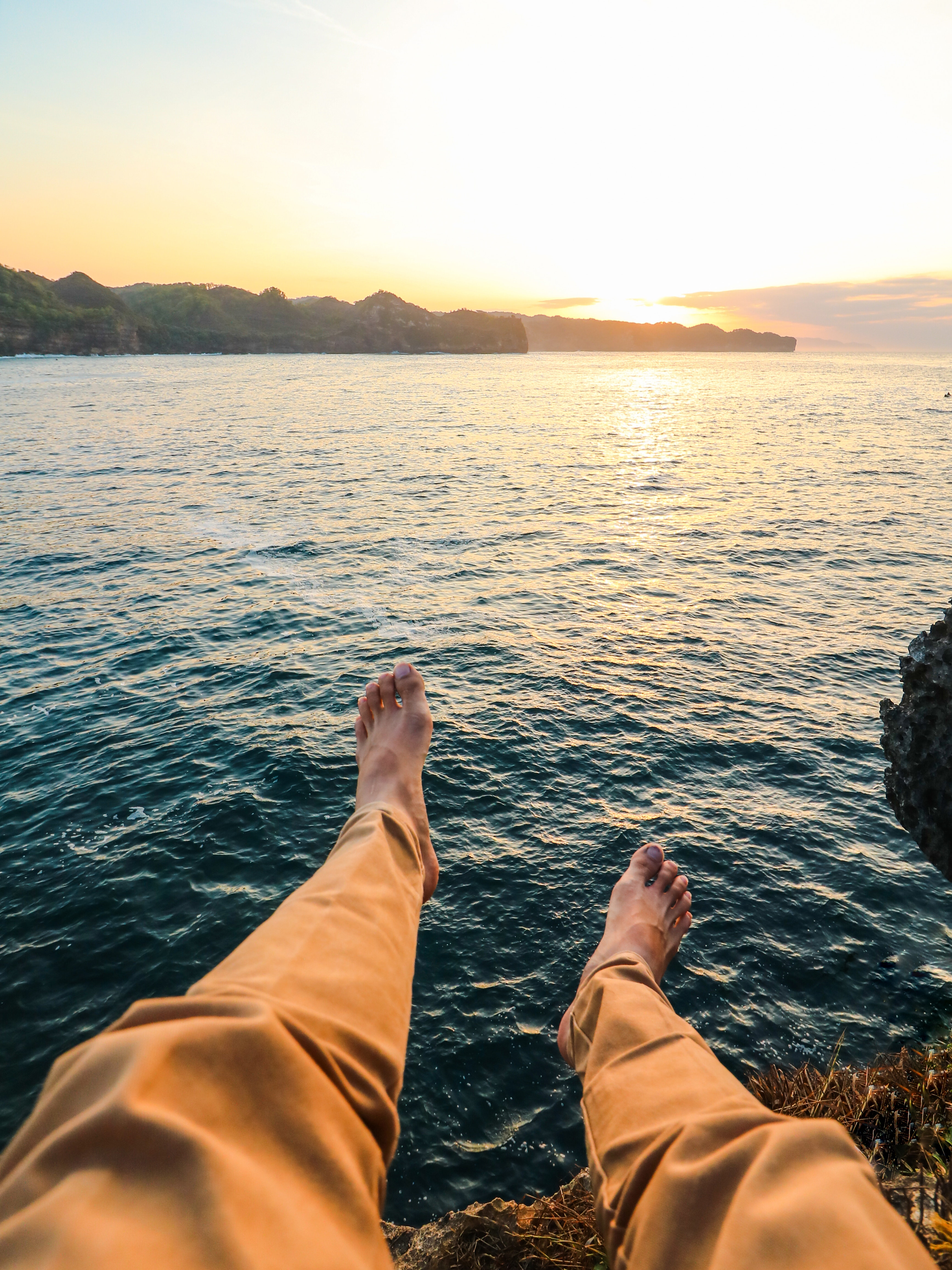 Person wearing yellow pants sitting on rock surrounded by sea photo
