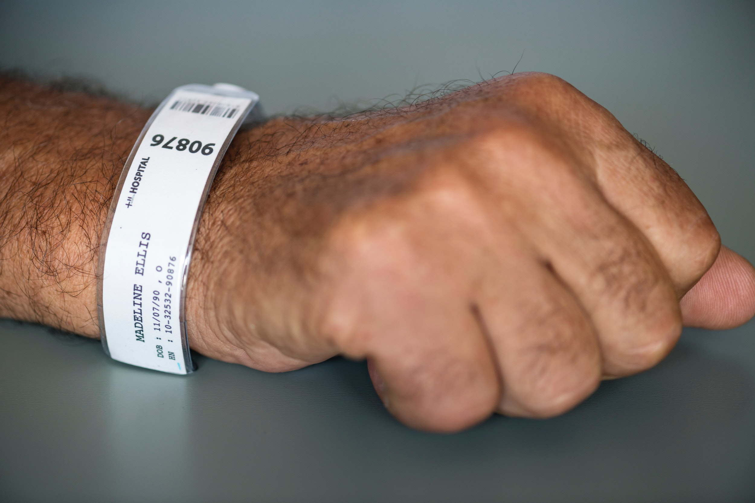 Person With Hospital Tag Labeled As Madeline Ellis 90876, Patient, Paper, Name, Modern, HQ Photo
