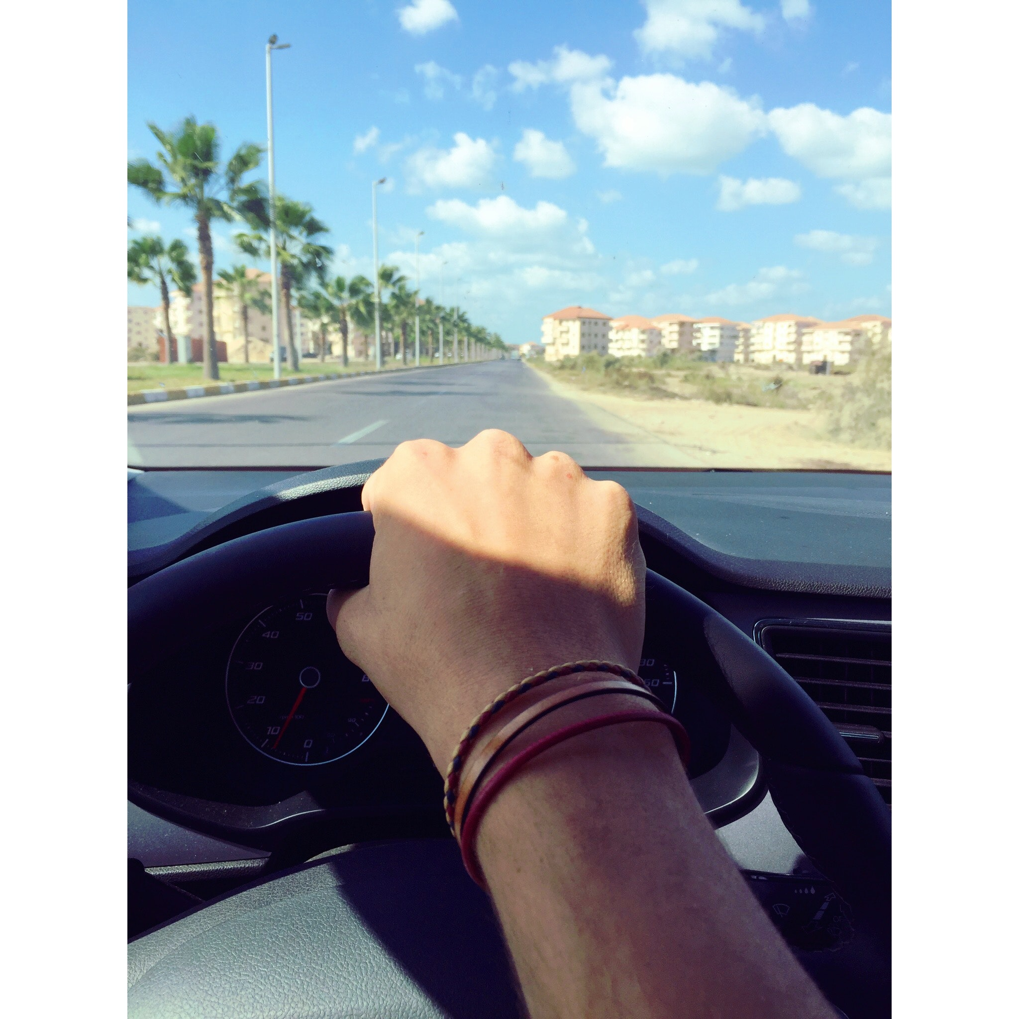 Person withe bracelets holding black steering wheel photo