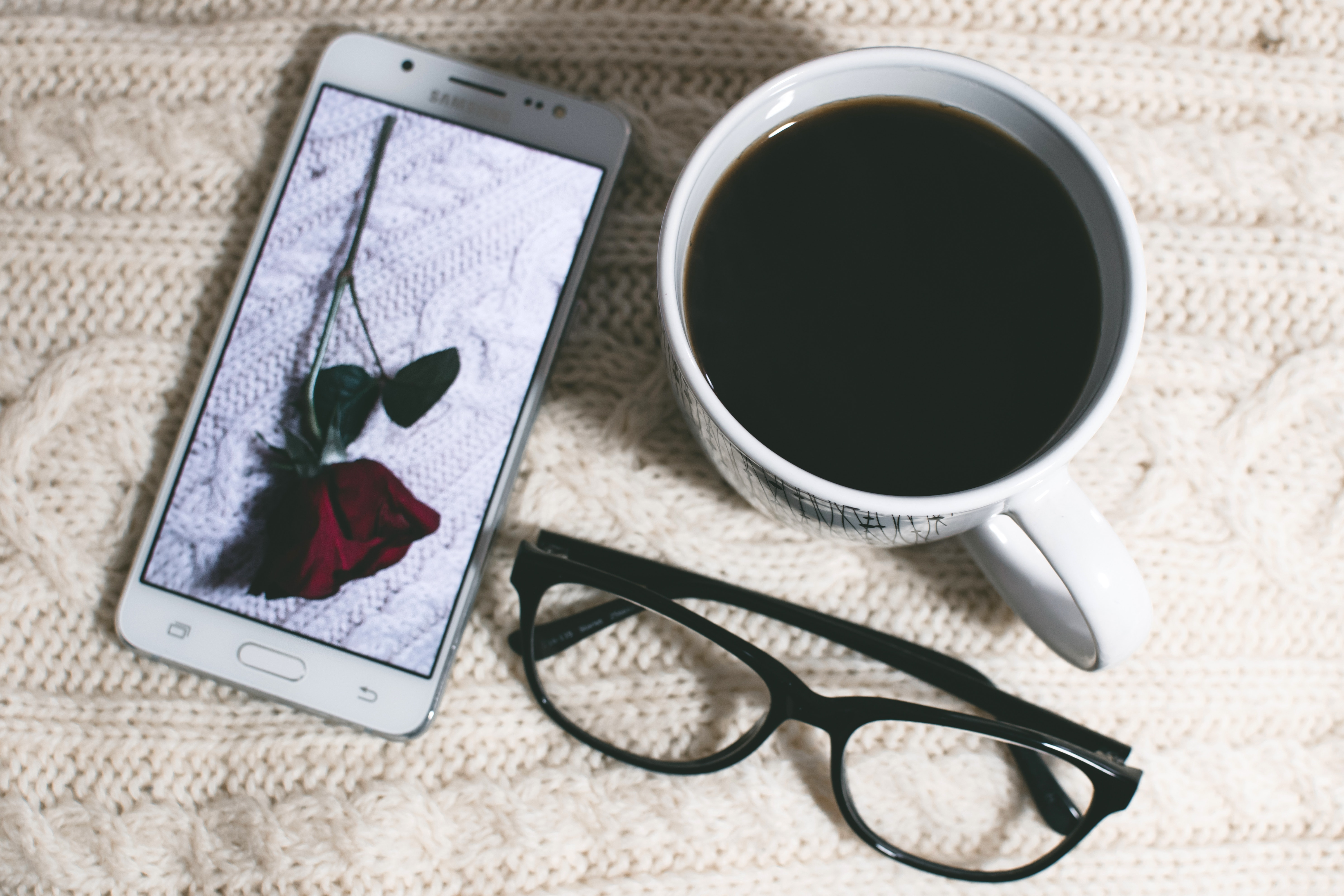 Phone near mug and eyeglasses on table photo