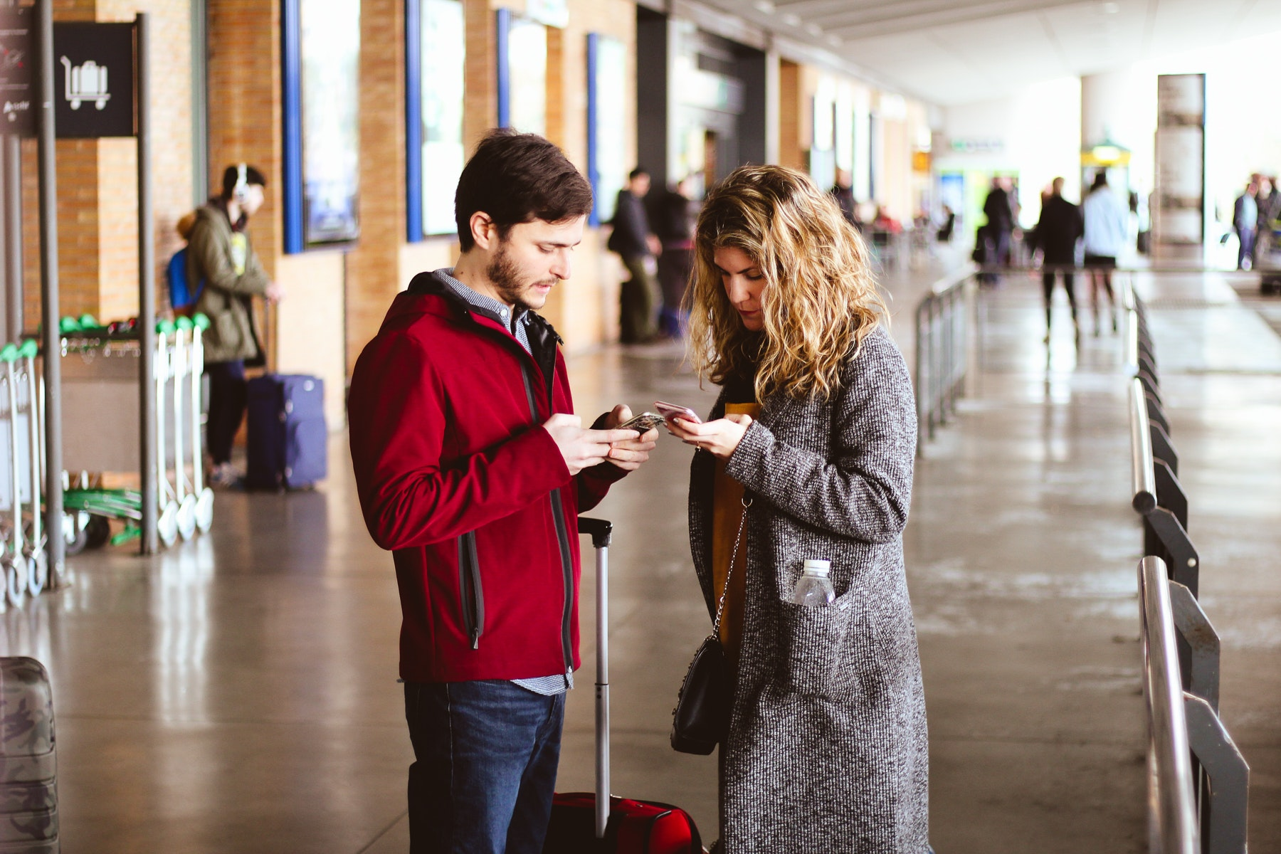 Photo of man and woman using their phones