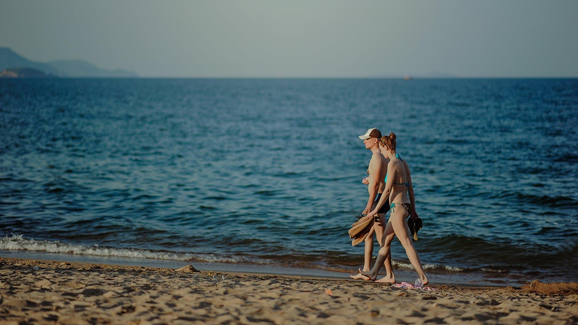Photo of man and woman walking on seashore