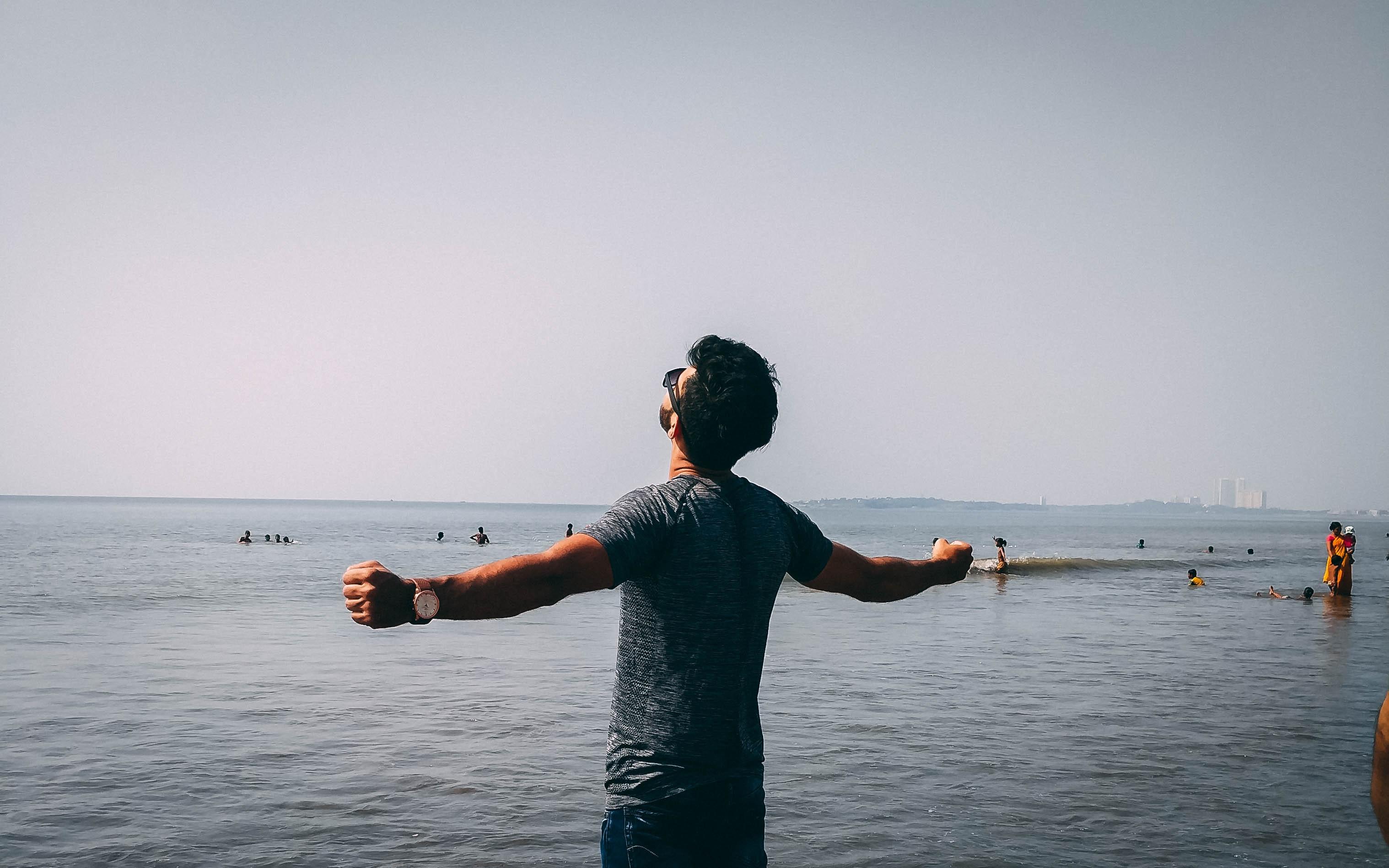Photo of man wearing gray shirt near sea