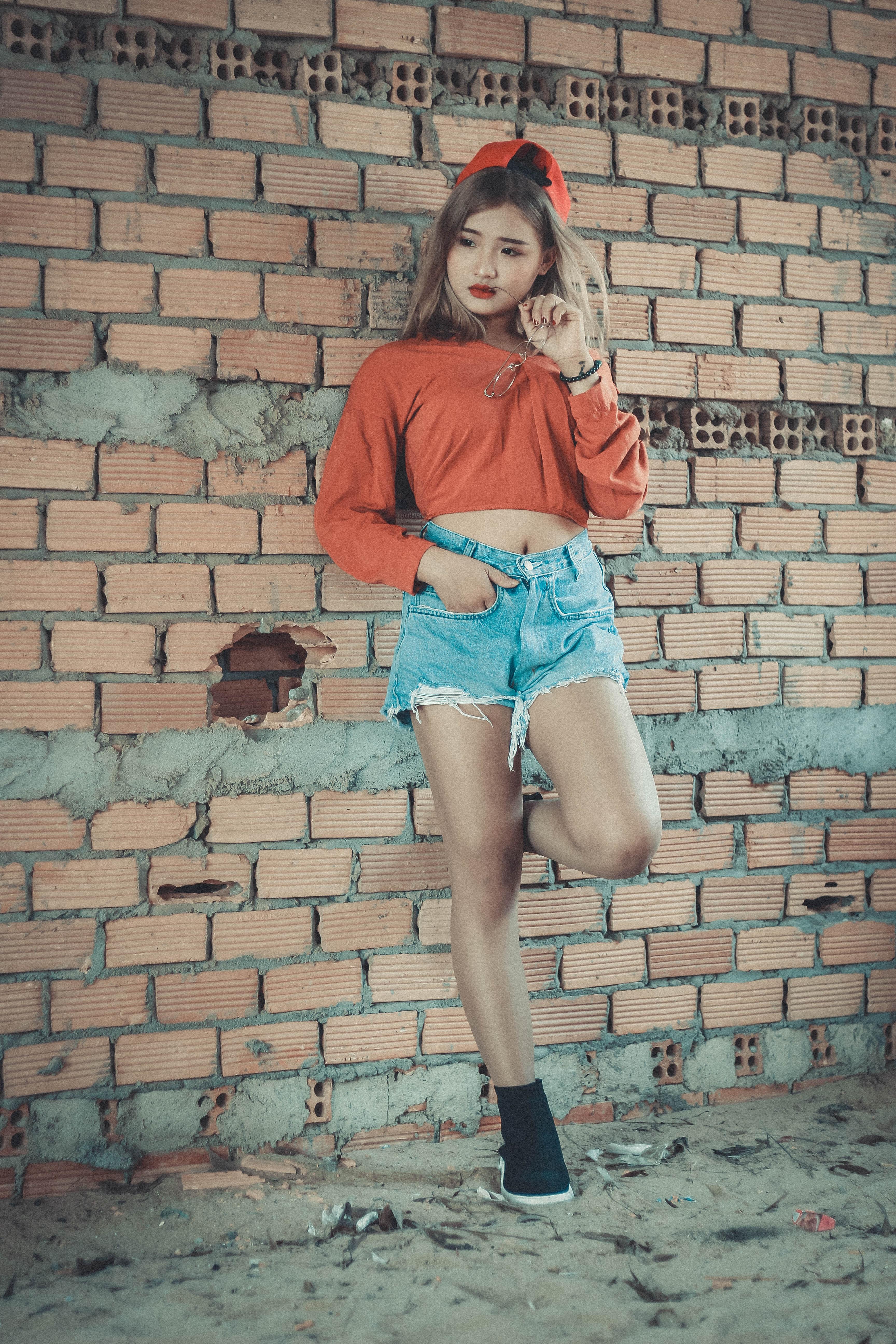 Photo of woman wearing orange crop-top near brown concrete brick wall