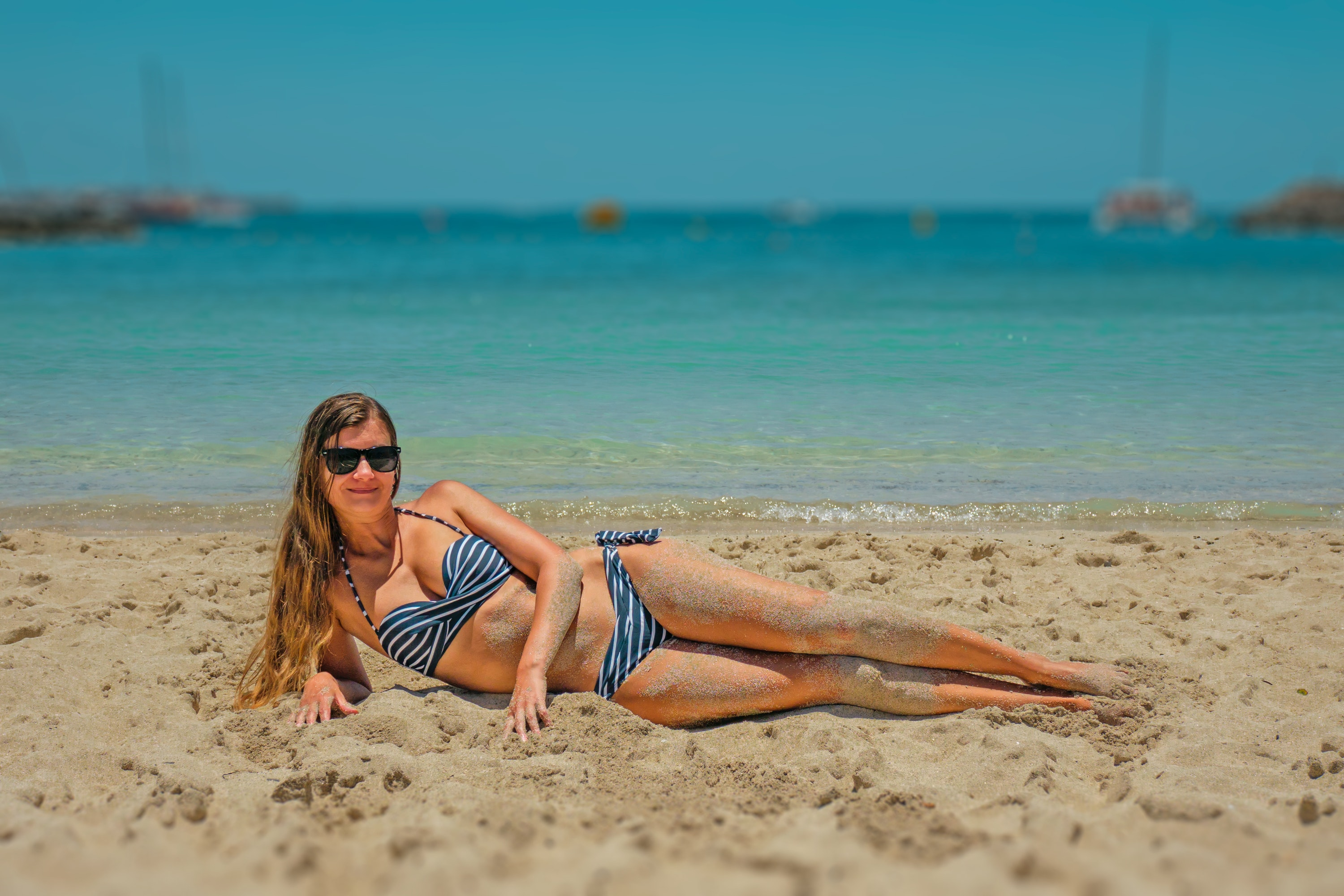 Woman in Blue and Black Bikini Lying on Beach Sand · Free Stock Photo