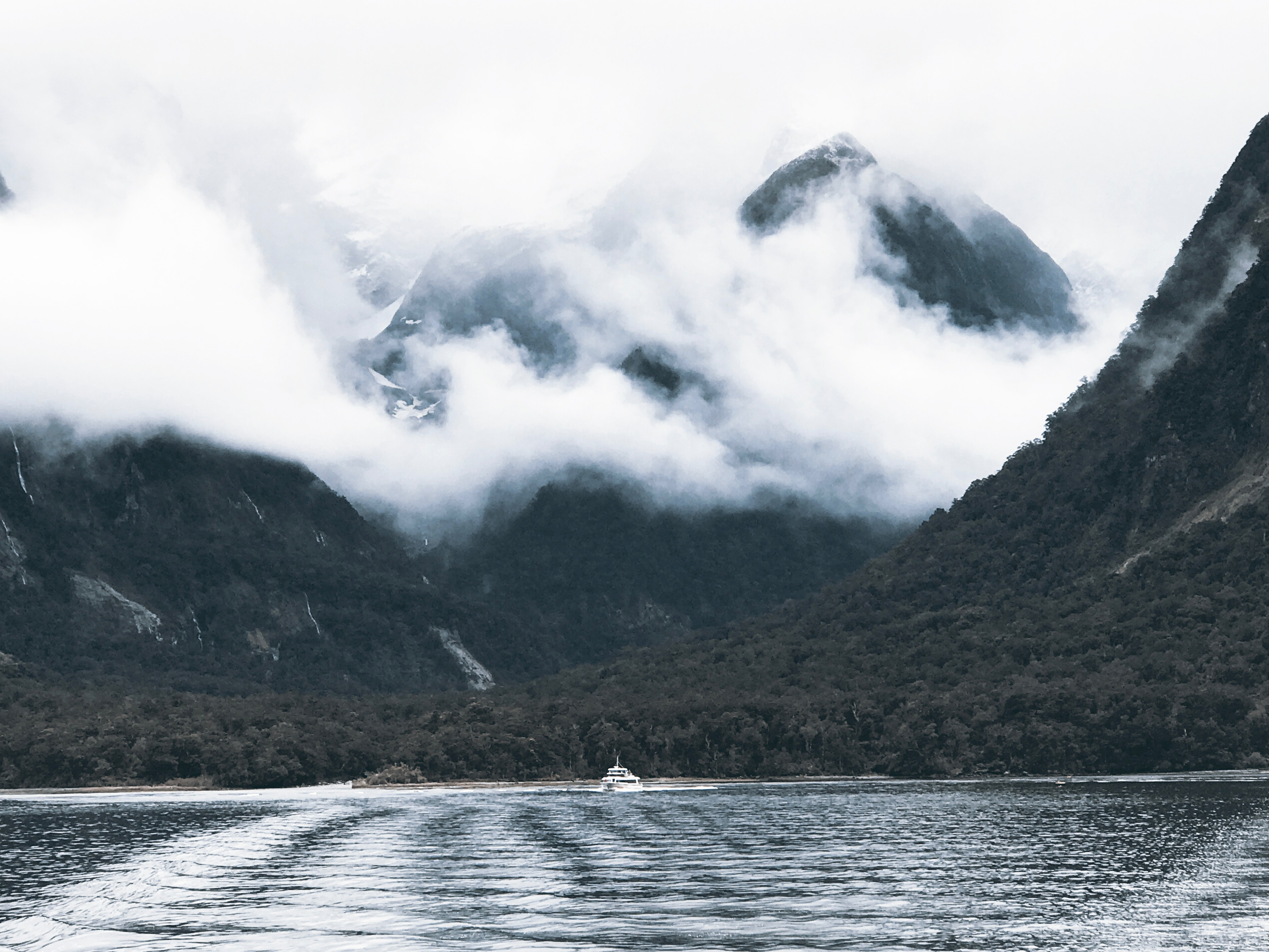 Photography of body of water surrounded by mountains and fogs