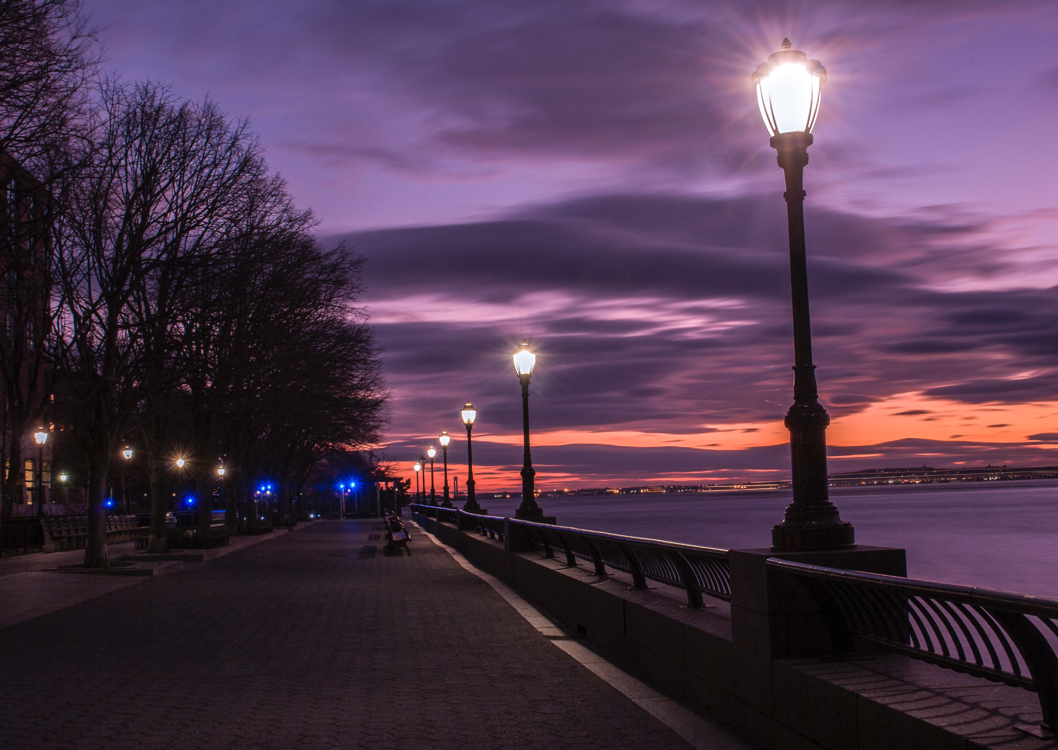 Photography of turned on street lamps beside bay during night time
