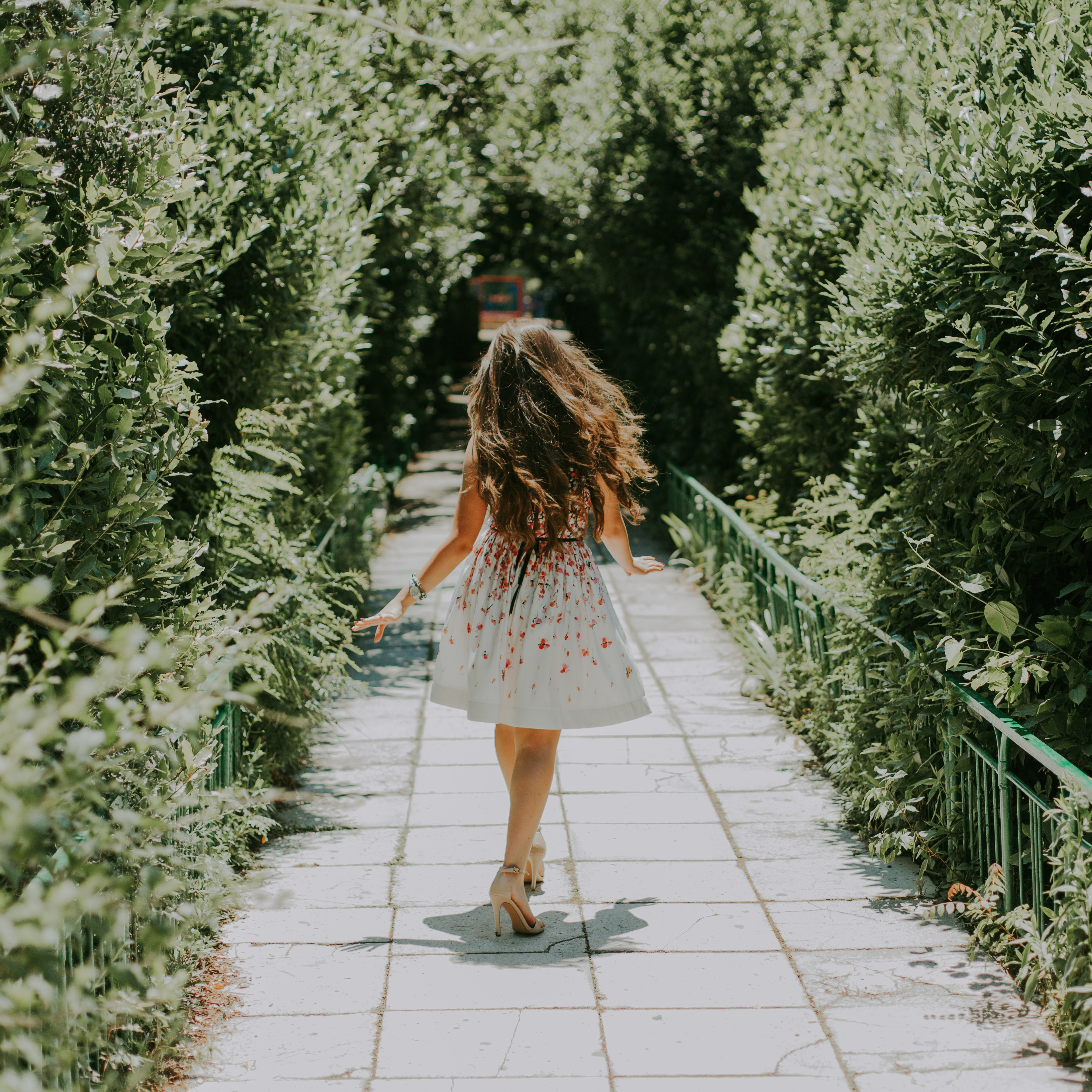 Photography of woman in white and red floral midi dress walking on pathway