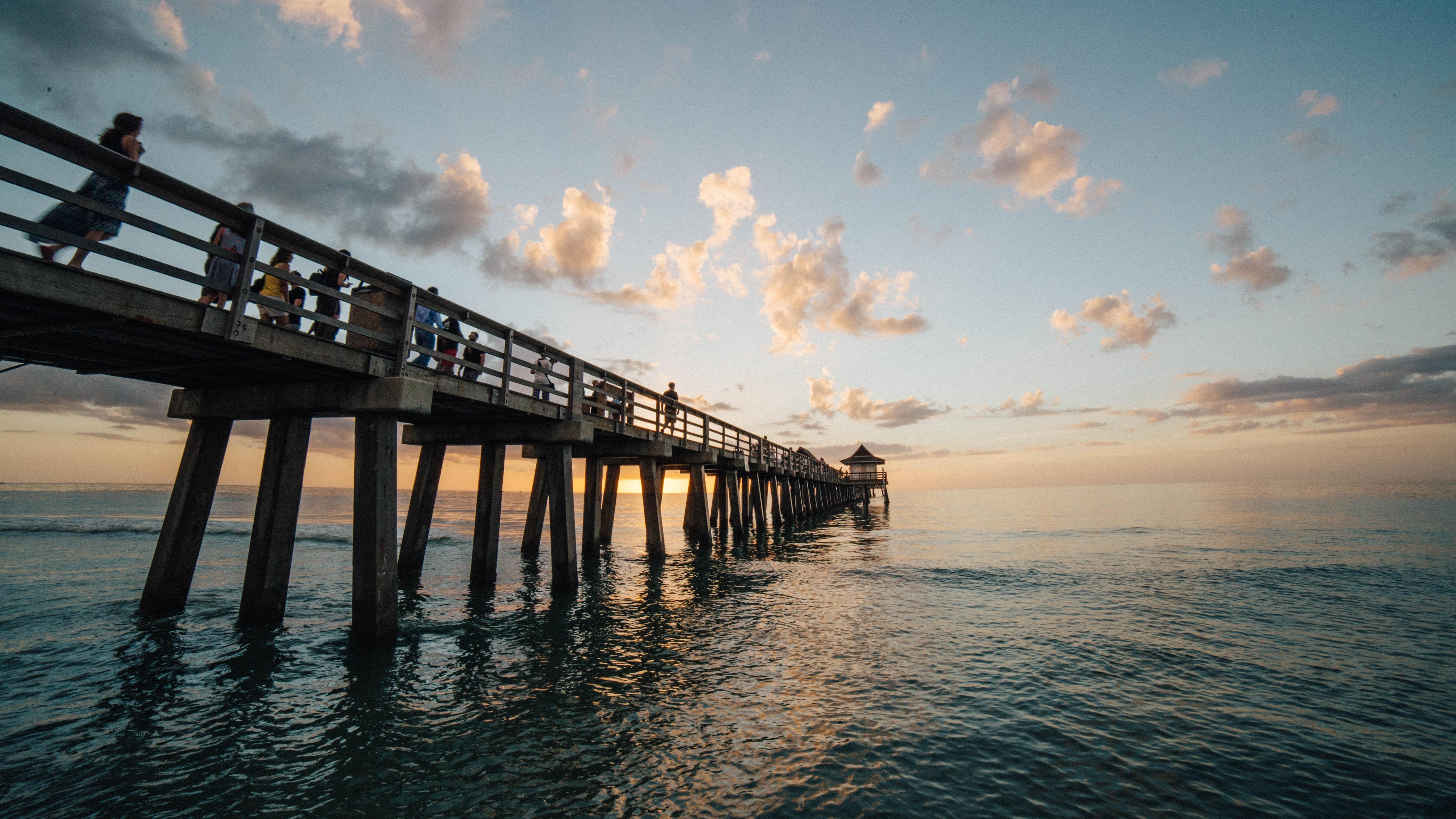 Pier on sea against cloudy sky photo