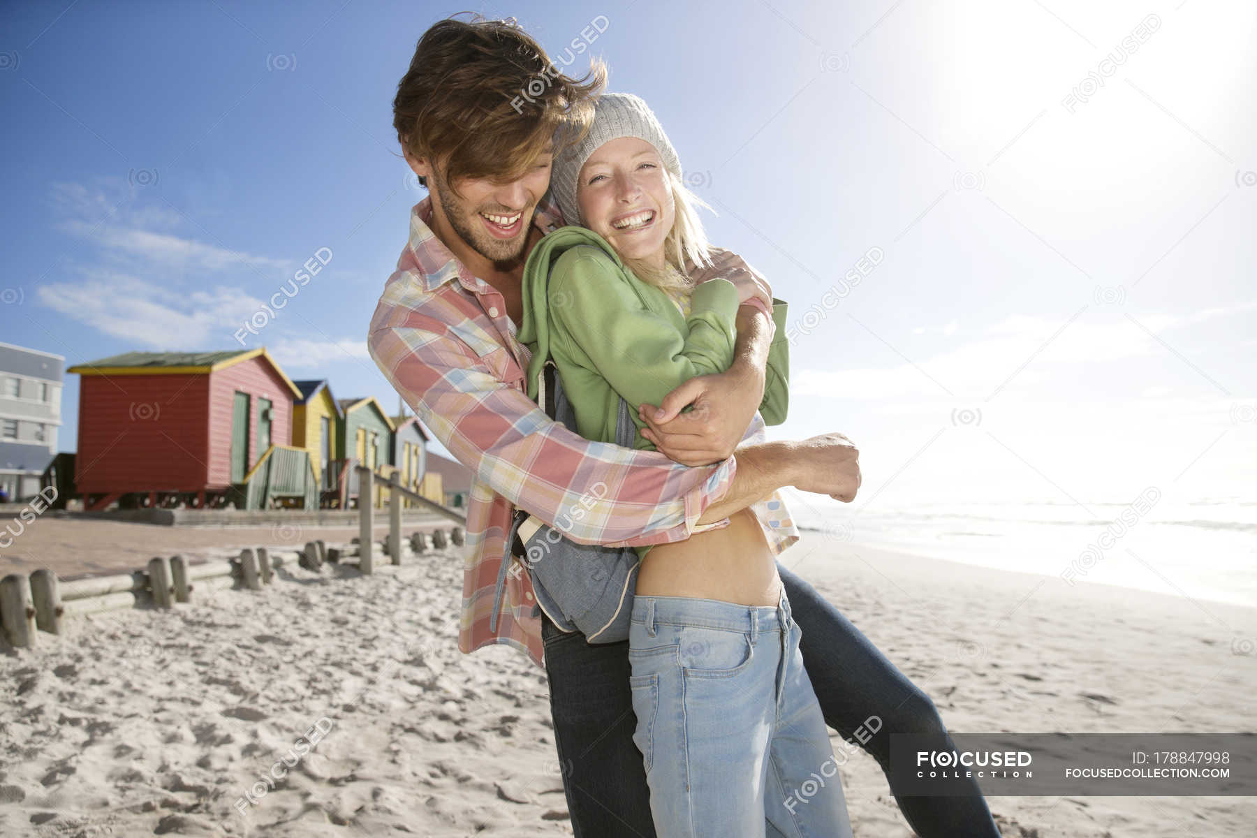 Playful young couple on beach — Stock Photo | #178847998