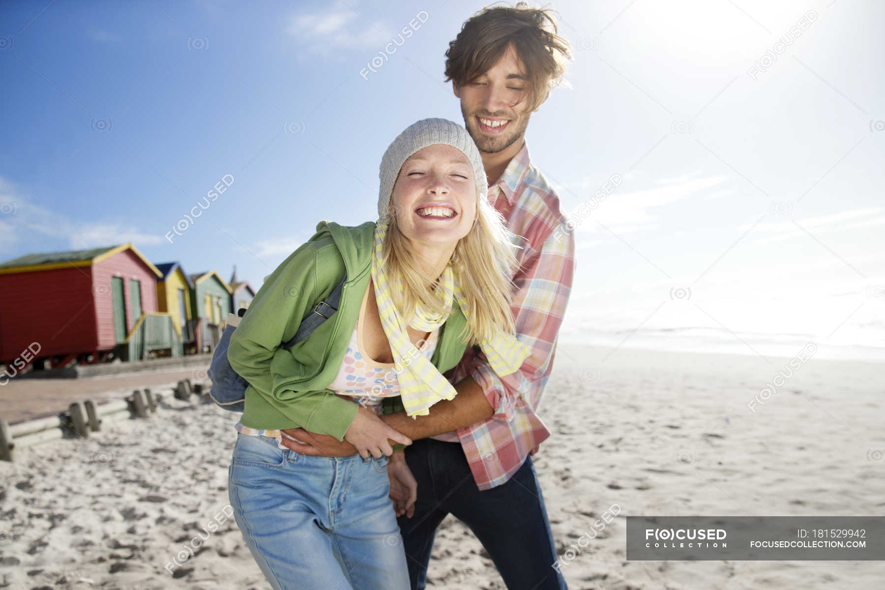 Playful young couple on beach — Stock Photo | #181529942