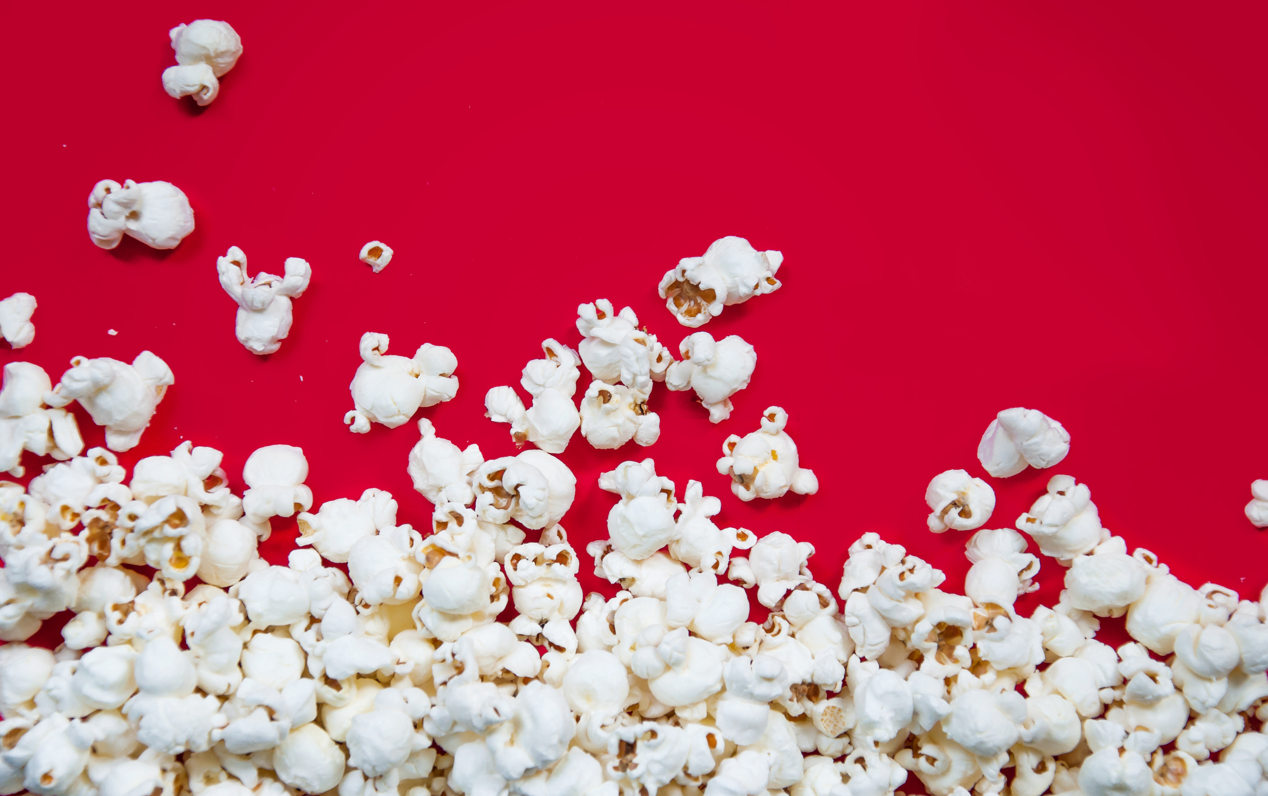 Popcorn spilled on red background photo