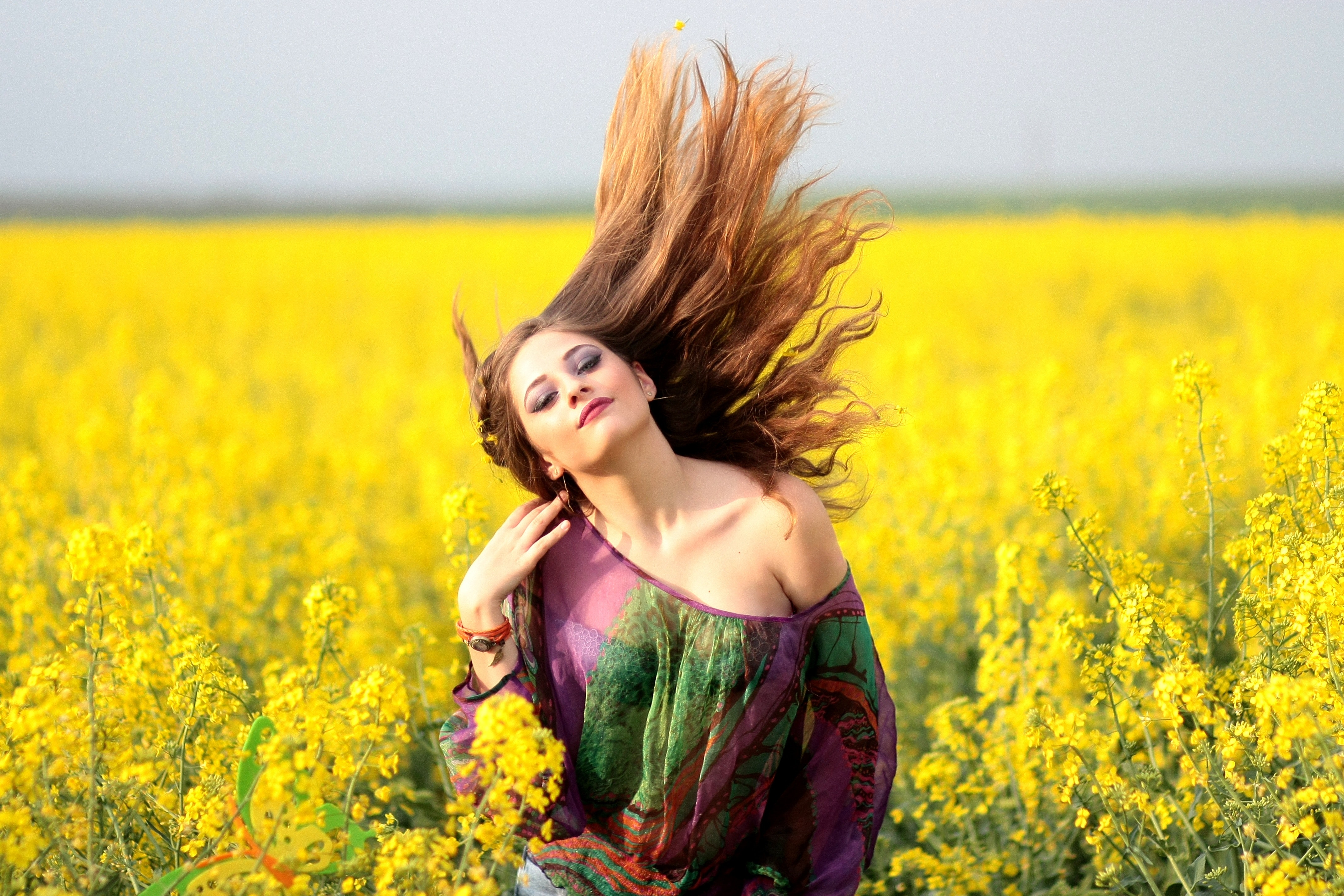 Portrait of young woman with yellow flowers in field photo