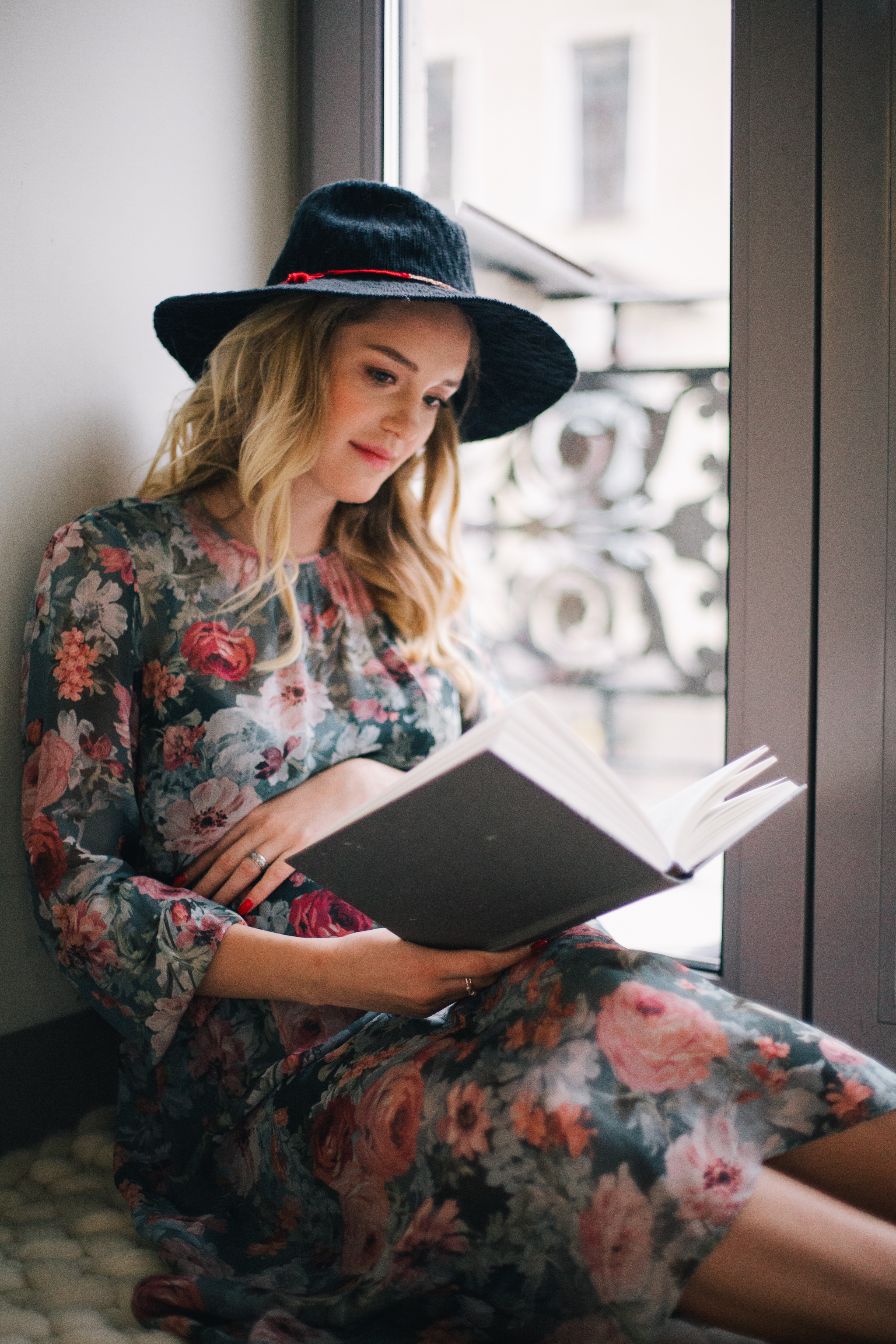 Pregnant woman wearing green, red, and white floral dress reading a book near window photo