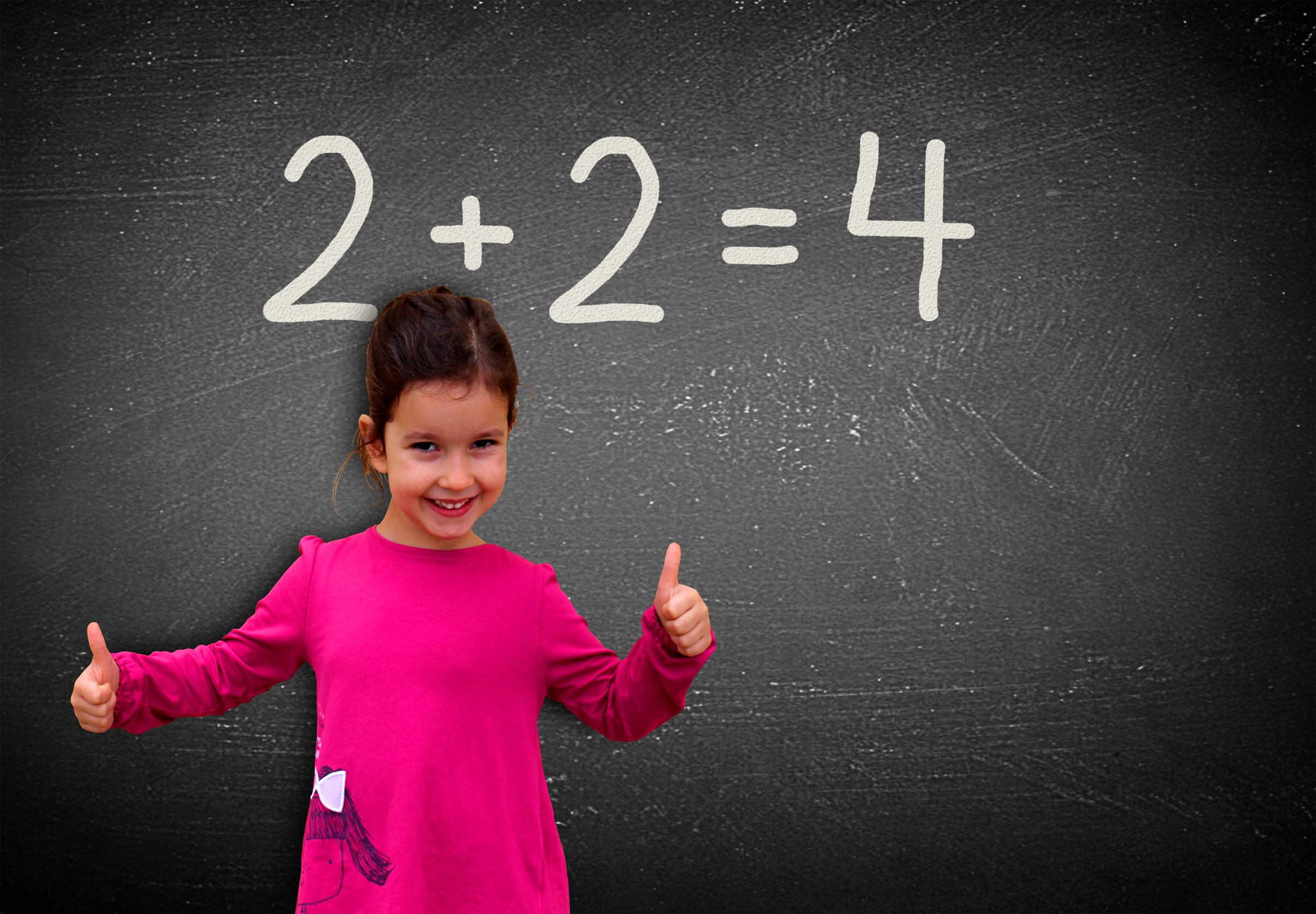 Proud assertive little girl solving a sum on blackboard photo