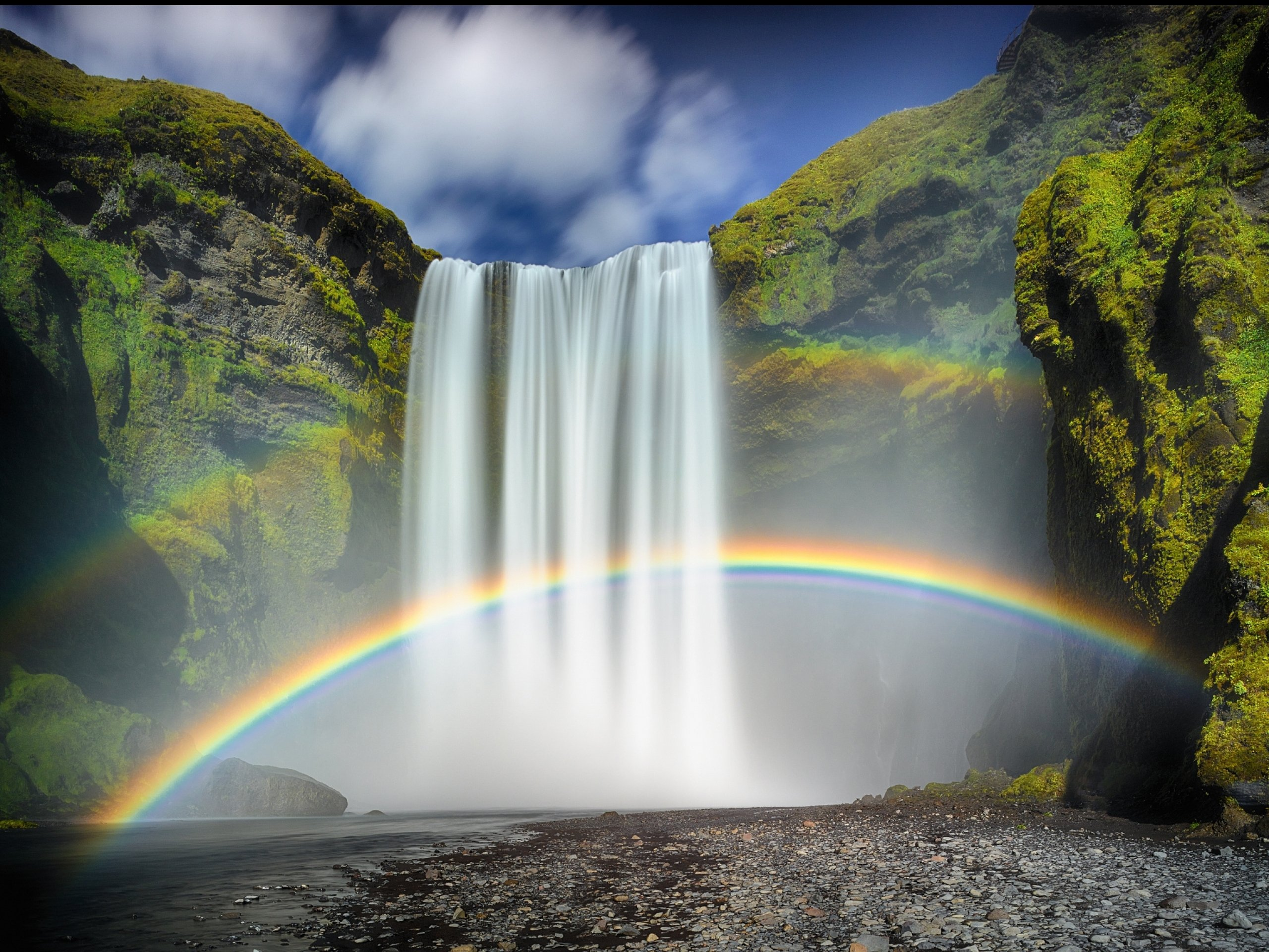Rainbow by waterfall photo