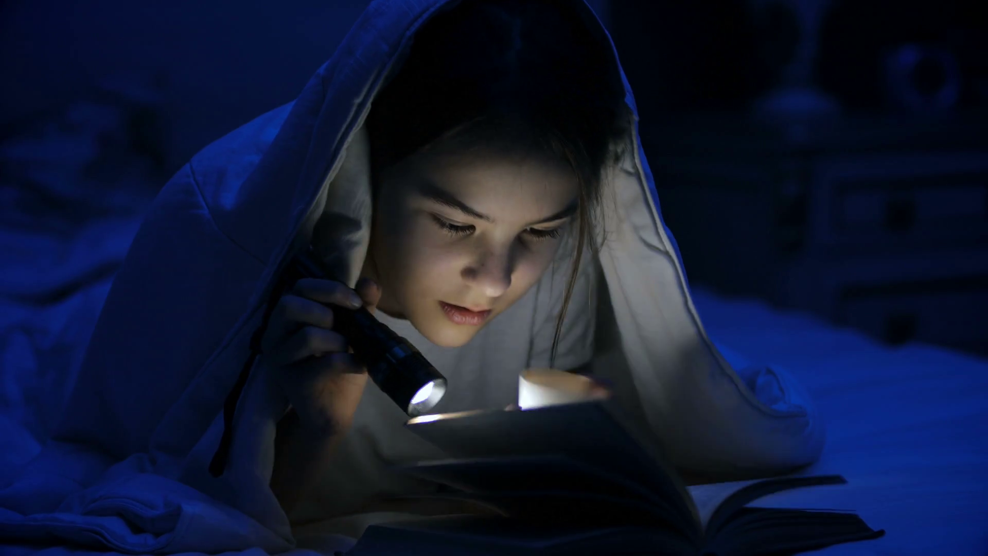 4k video of girl with flashlight reading scary story under blanket ...