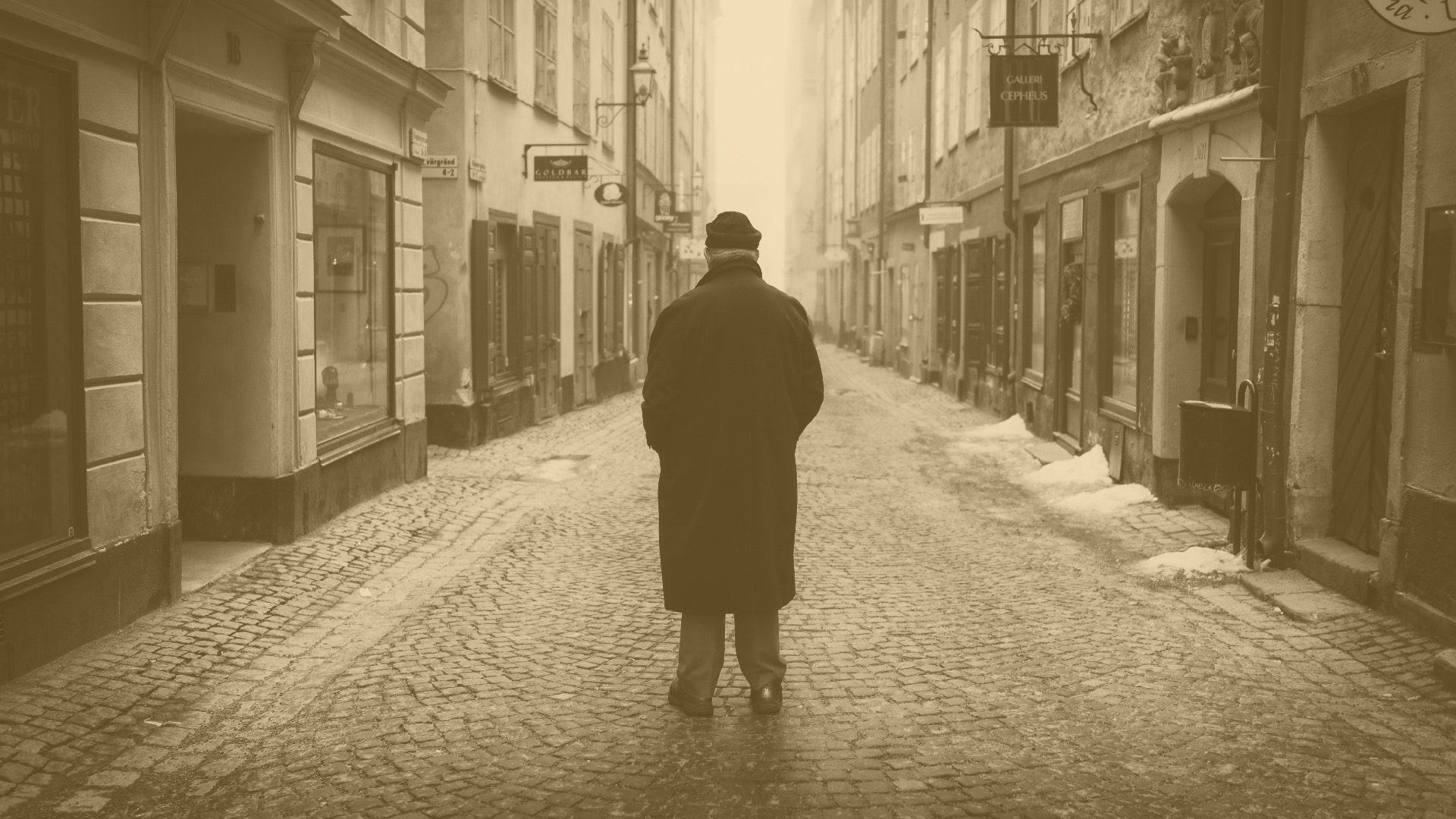 Rear view of a man walking on cobblestone photo
