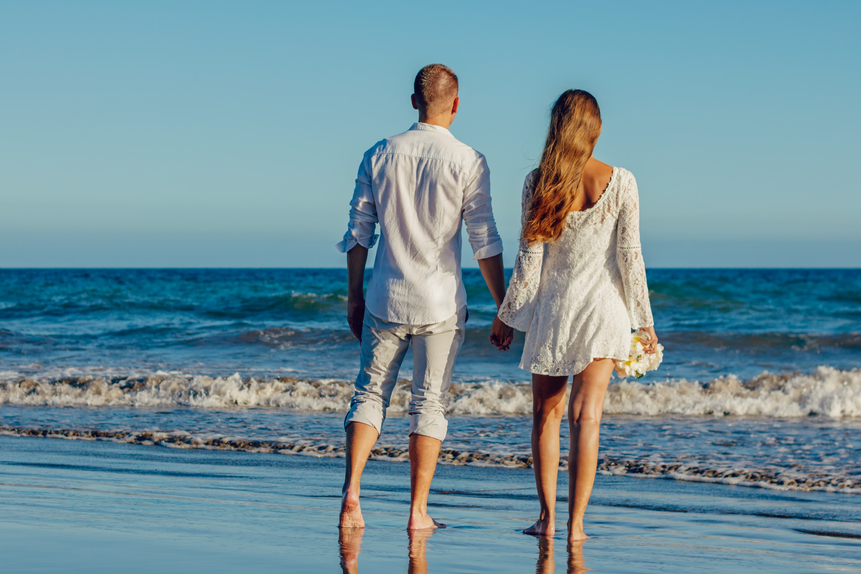Rear view of couple on beach against clear sky photo