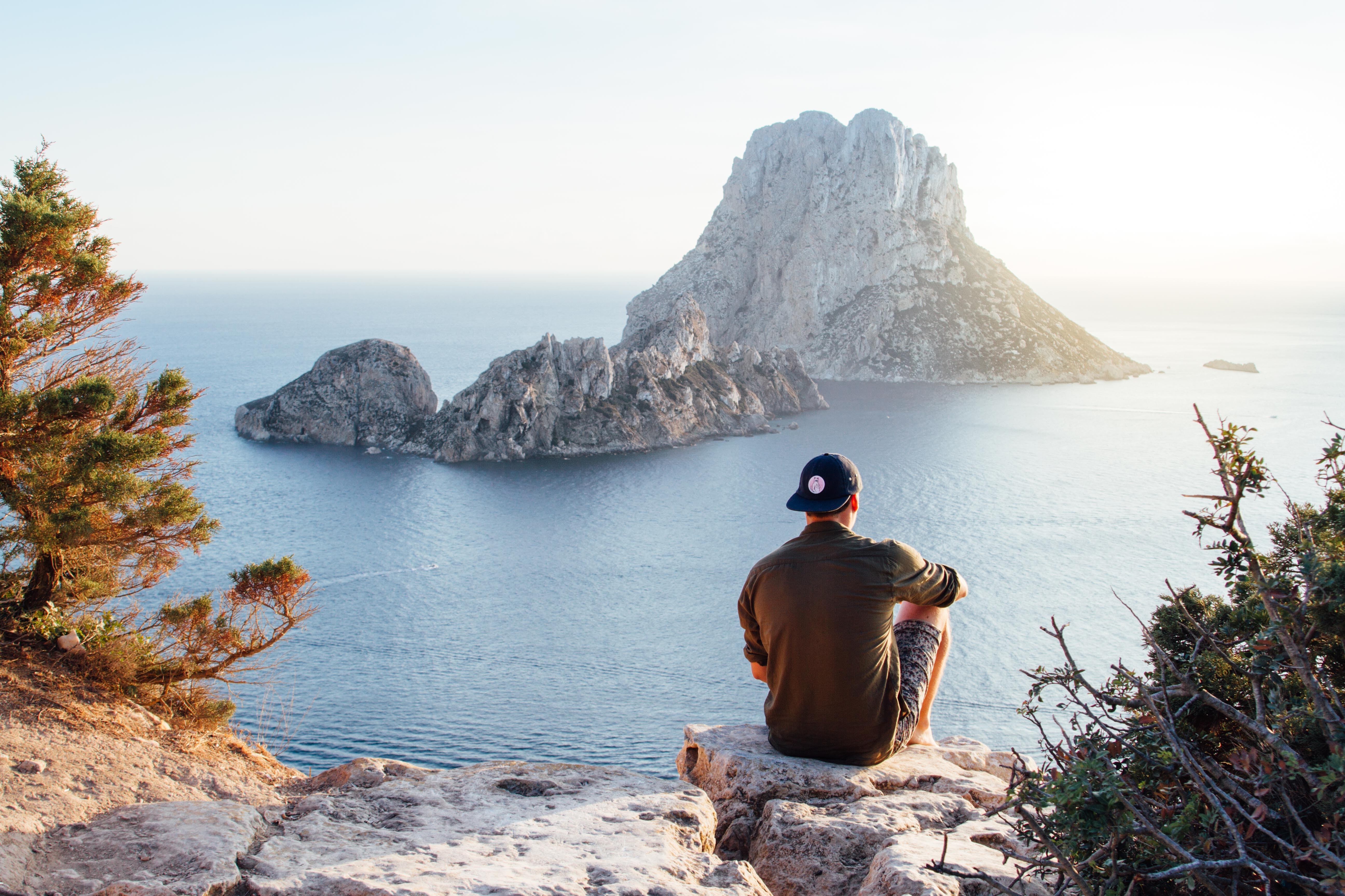 Rear view of man sitting on rock by sea photo