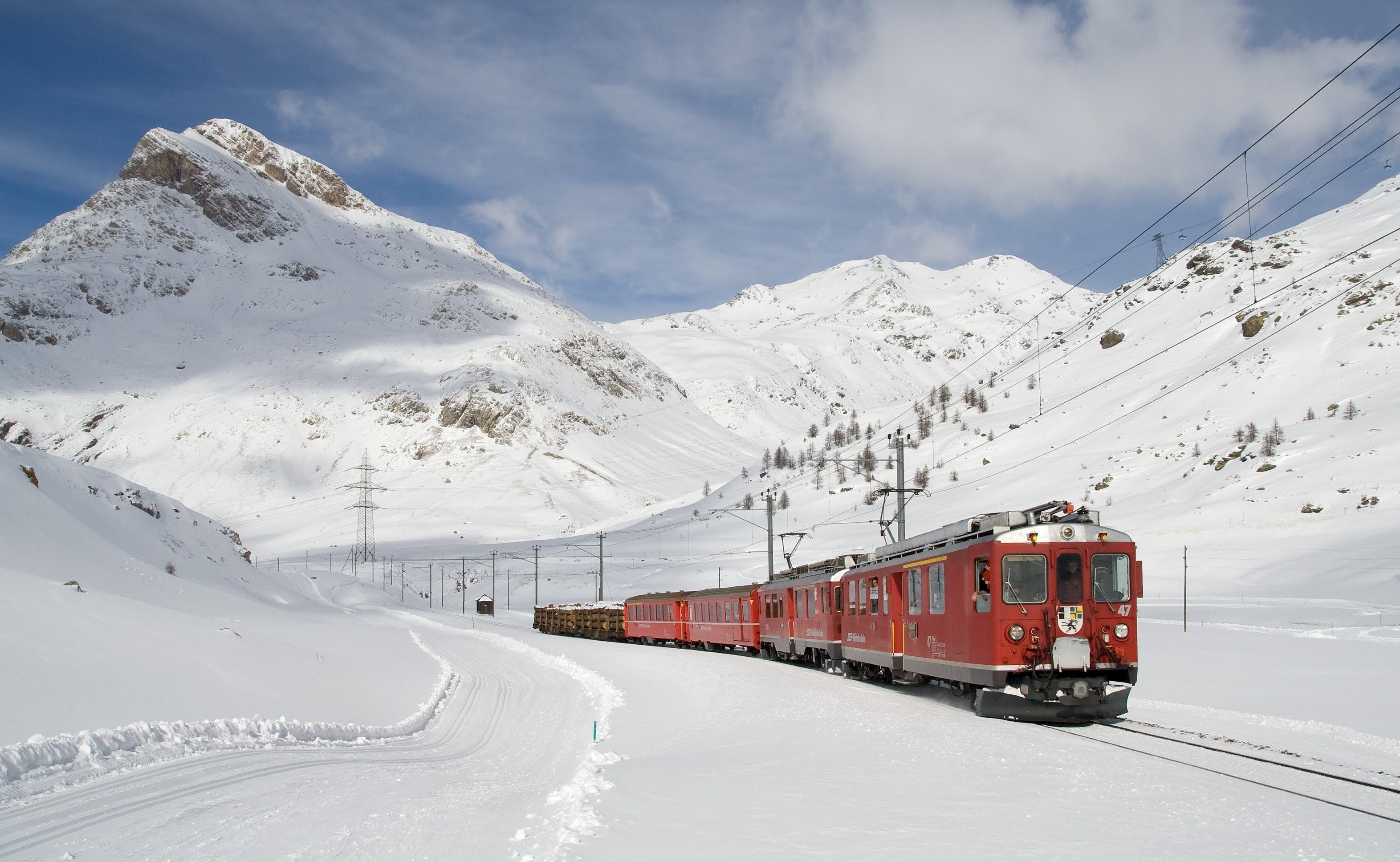 Red and black train running along snow covered field photo