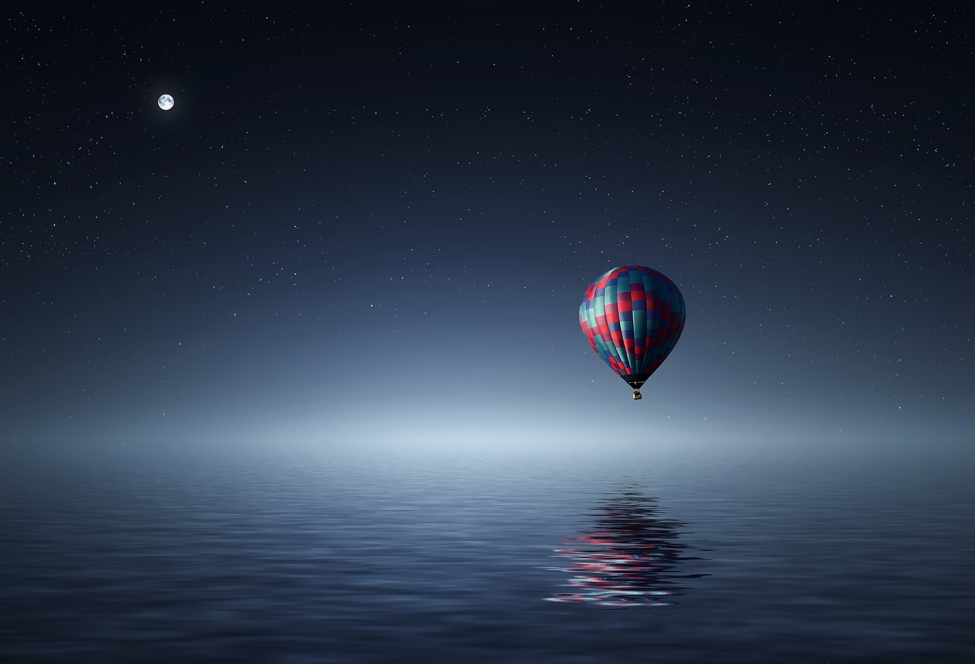 Red and blue hot air balloon floating on air on body of water during night time photo