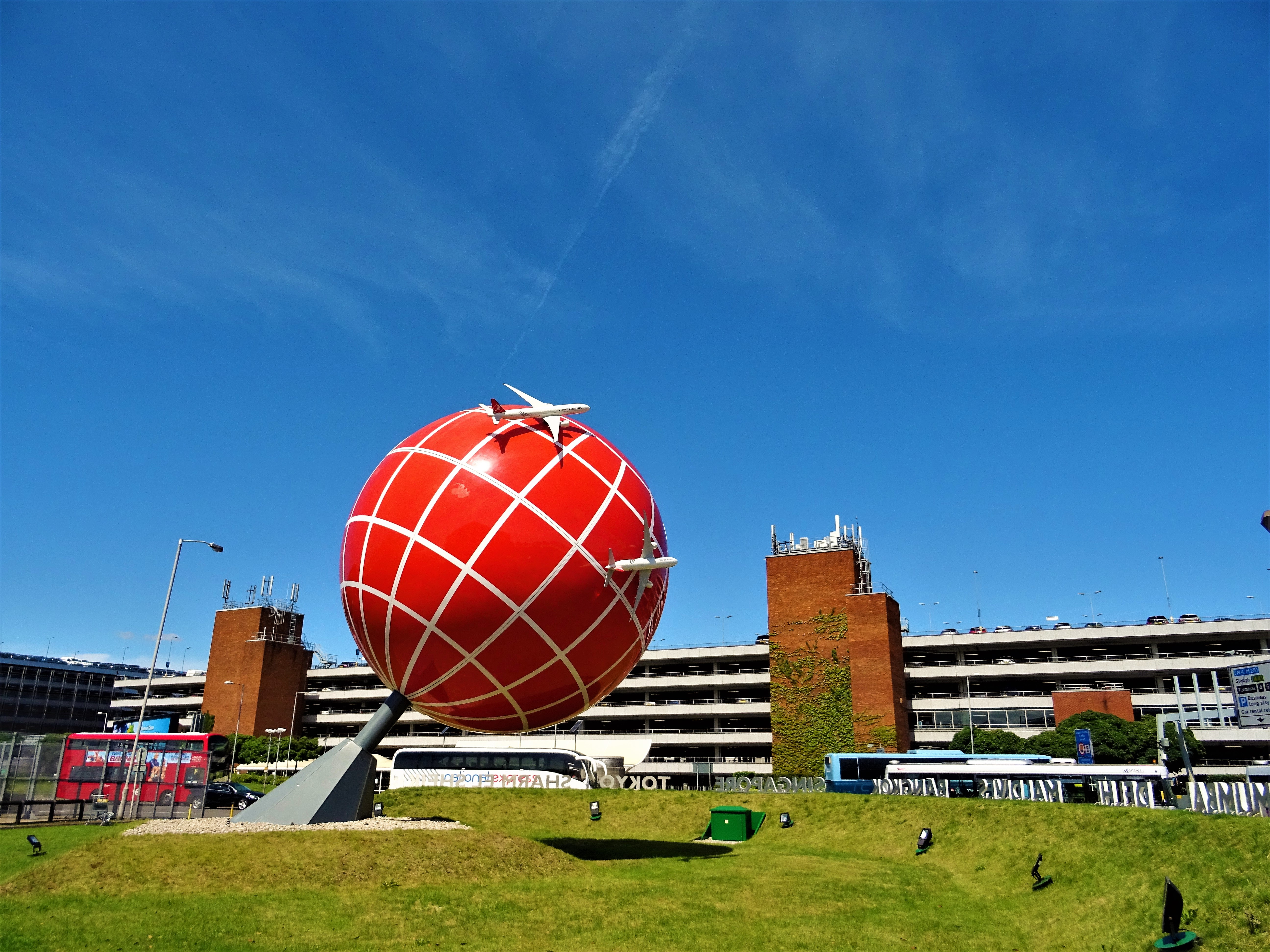 Red and white globe statue near brown and white concrete building photo