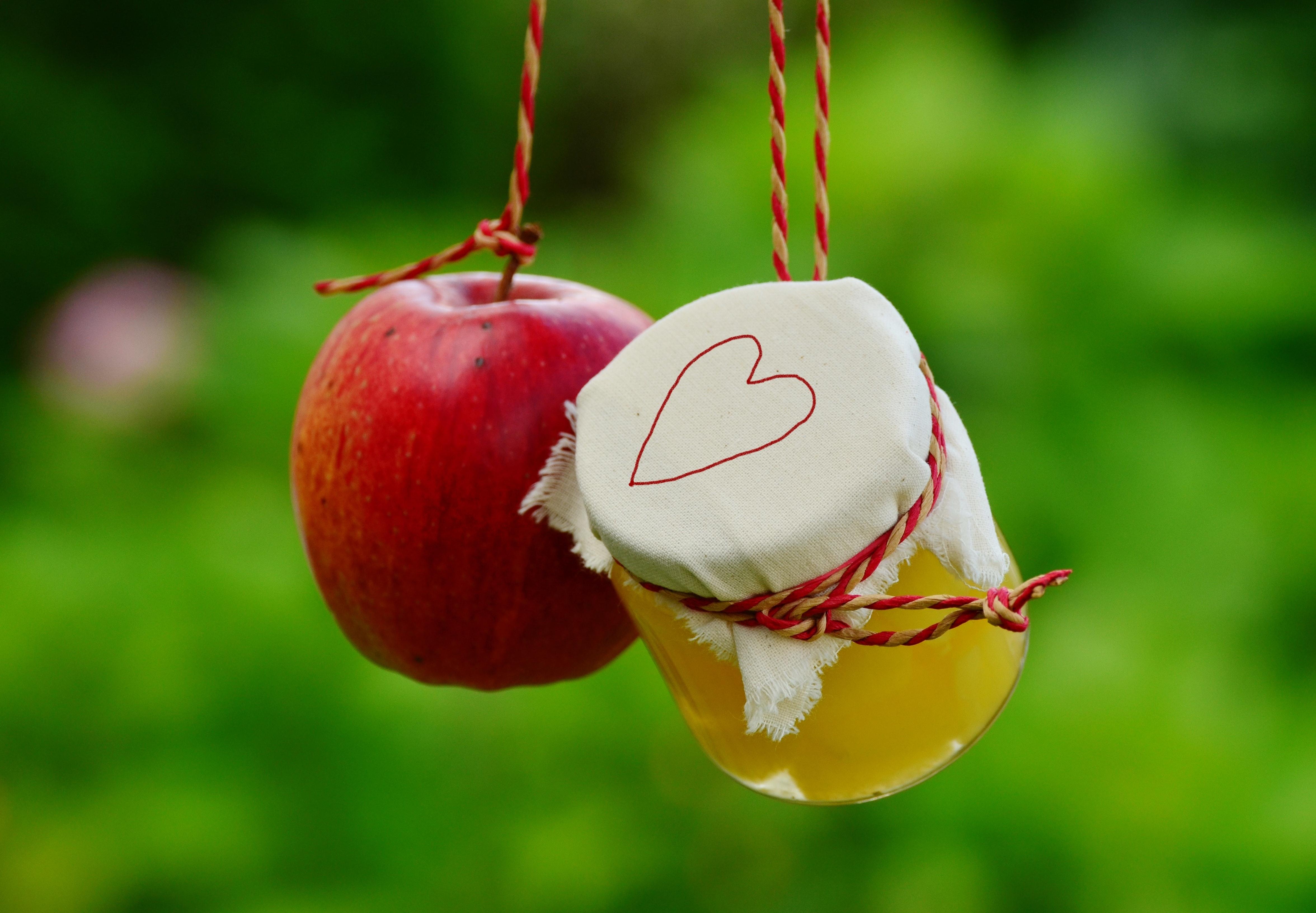 Red apple fruit beside clear glass jar photo