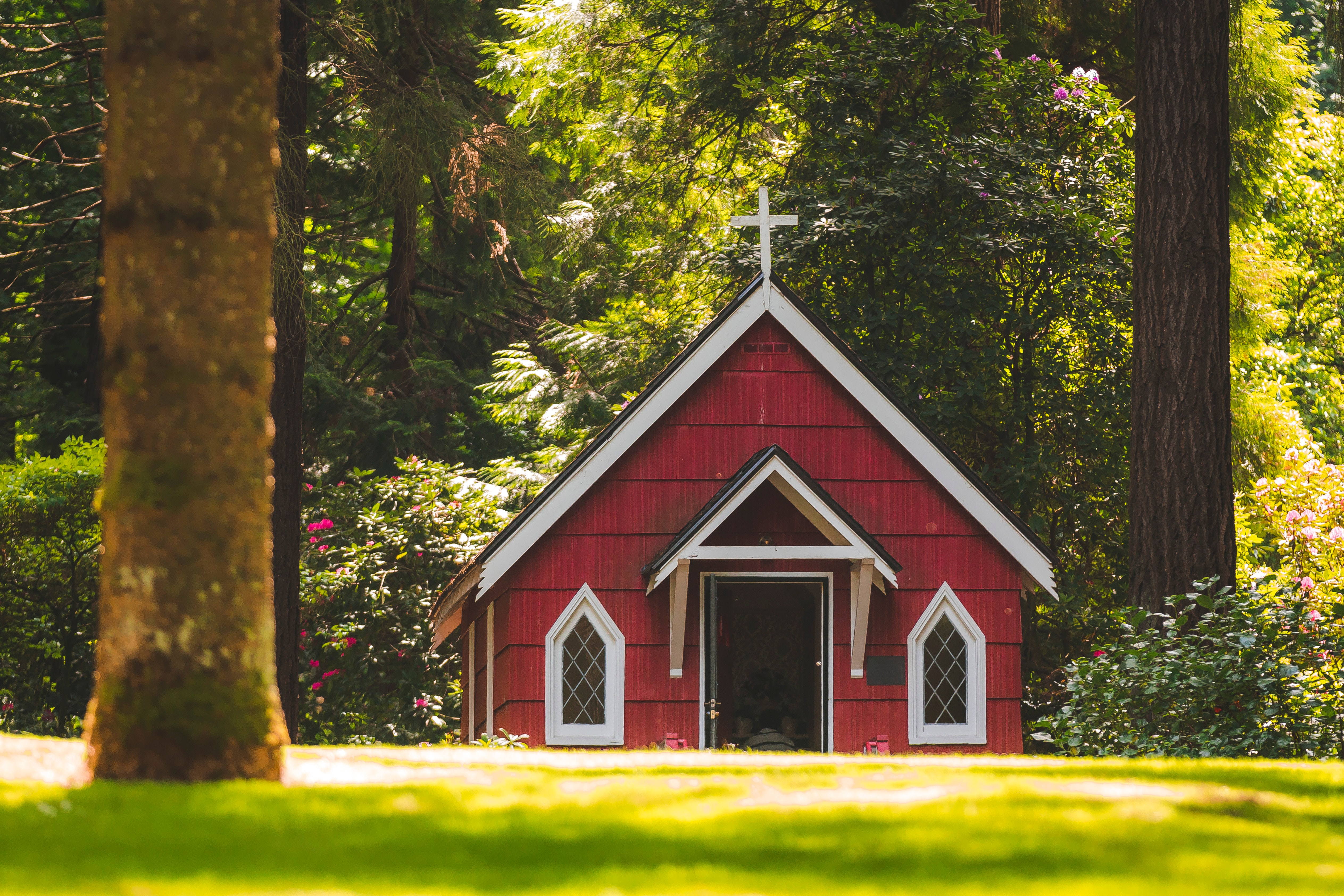 Red chapel on grassy field with trees photo