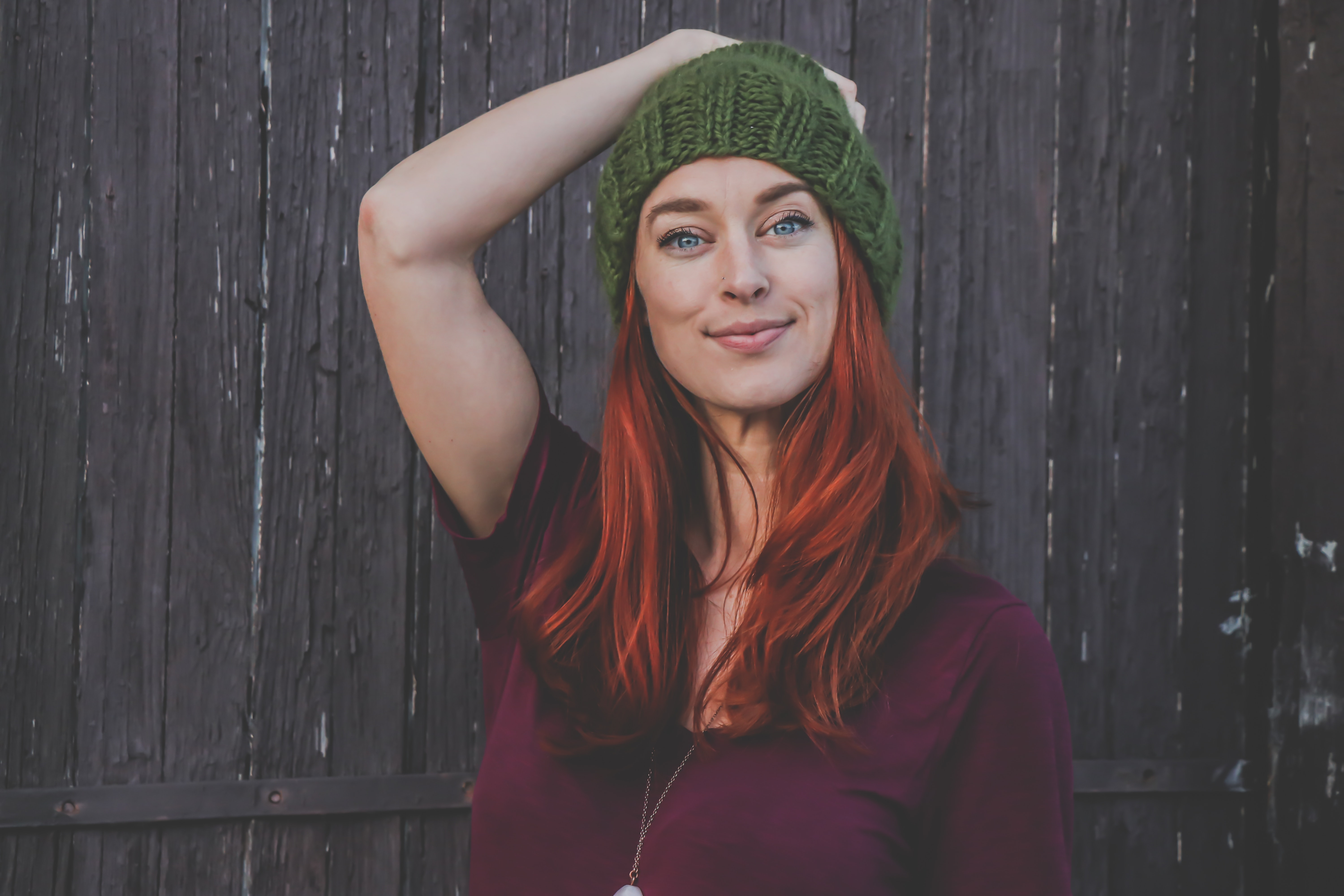 Red haired woman in maroon top wearing green beanie photo