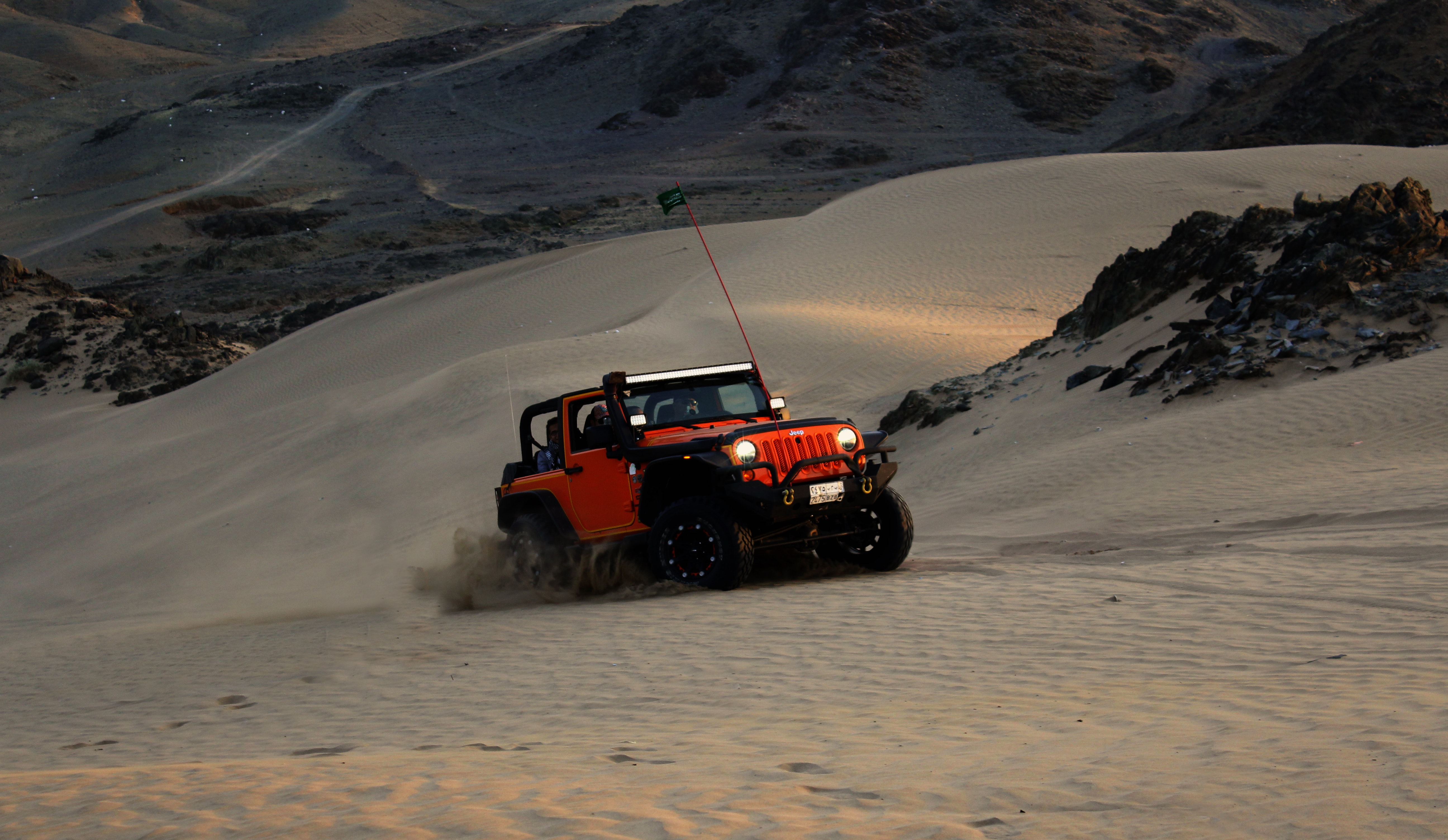 Red jeep wrangler on white covered field photo