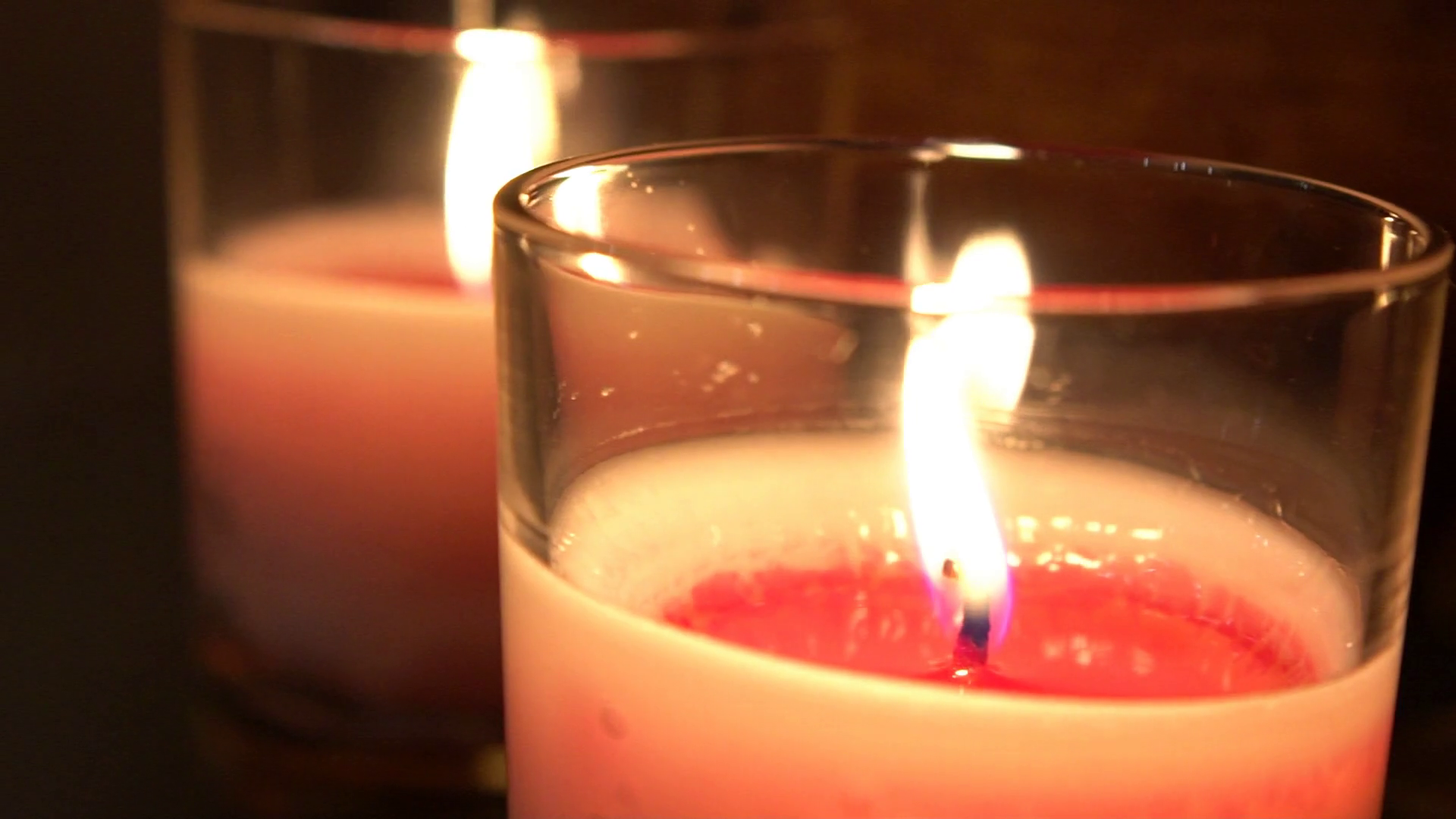 Slow motion of flame lighted red wax candle in the dark close-up ...