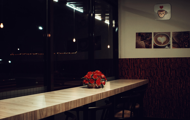 Red rose arrangement decor on brown wooden desk photo