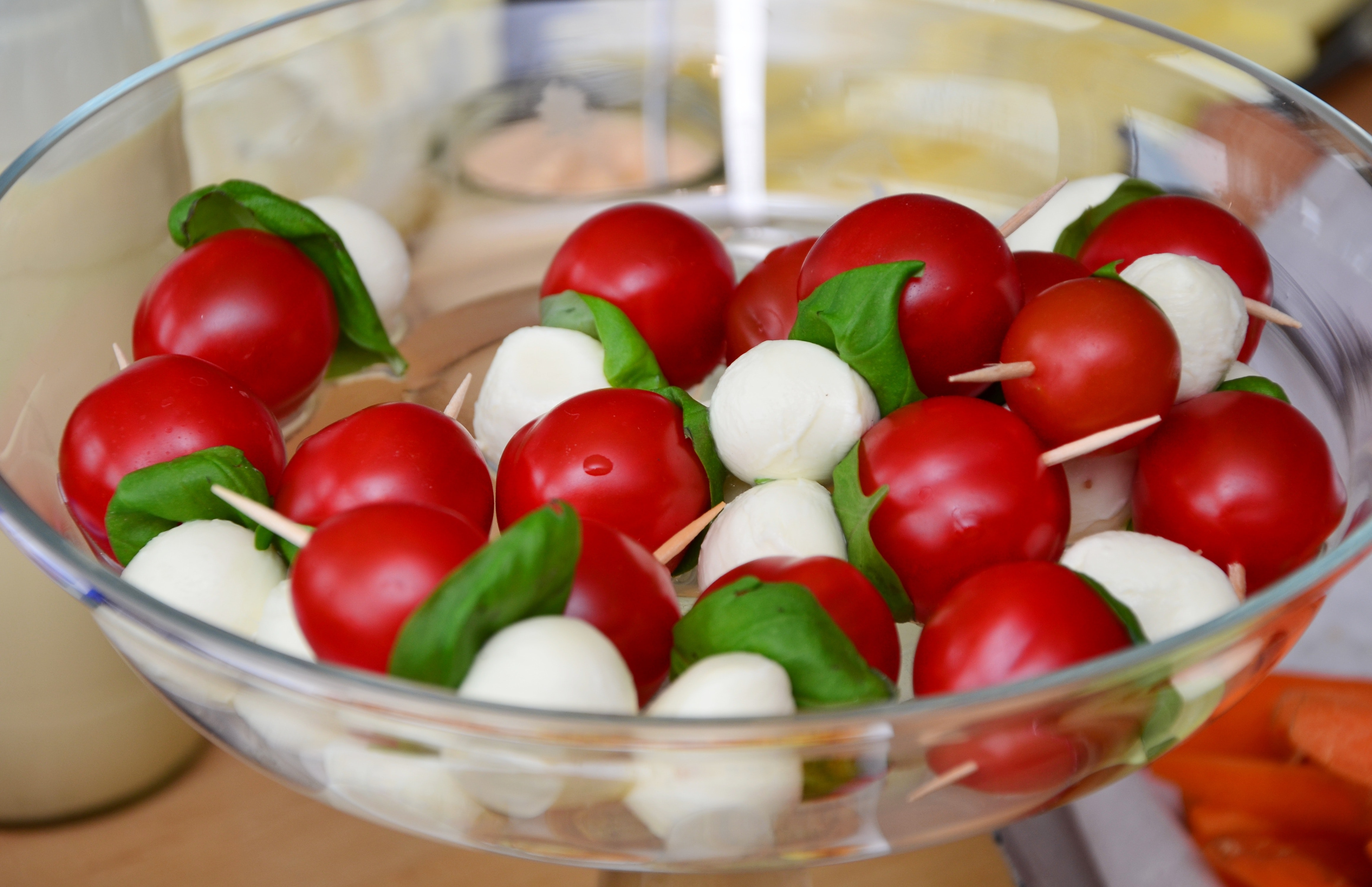 Red round fruit served on clear glass bowl photo