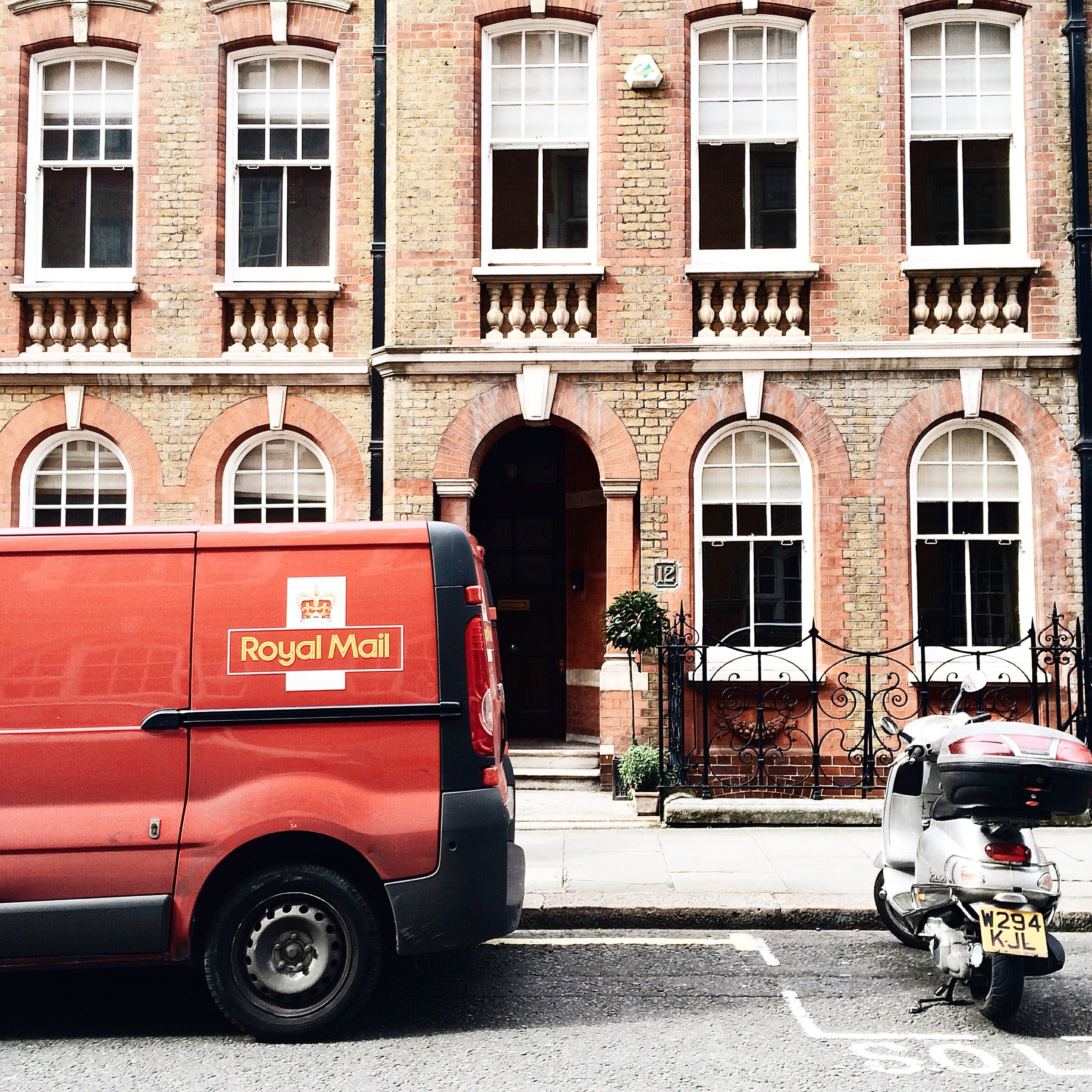 Red royal mail parked near brown brick building photo