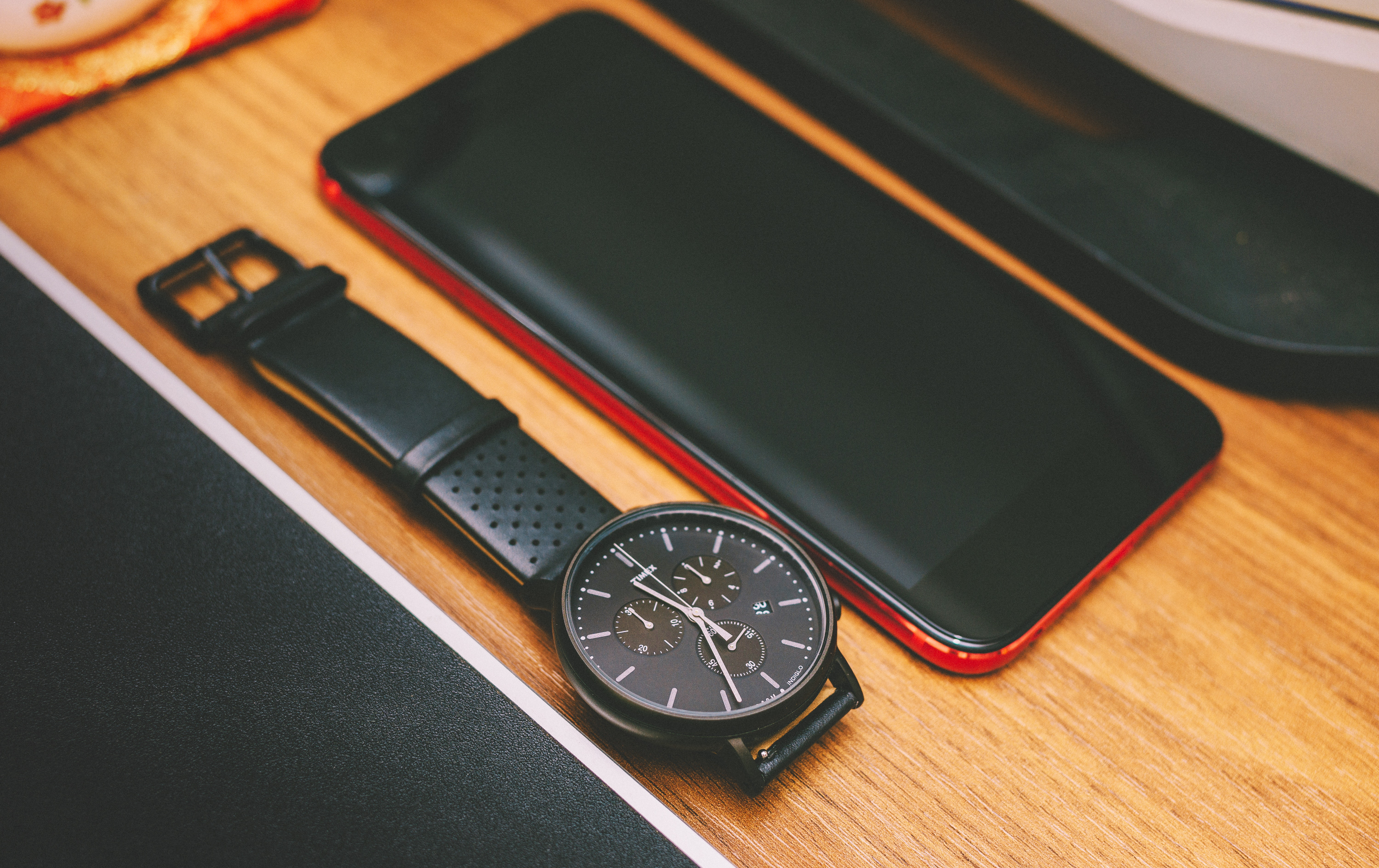Red smartphone beside the black chronograph watch on brown wooden board photo
