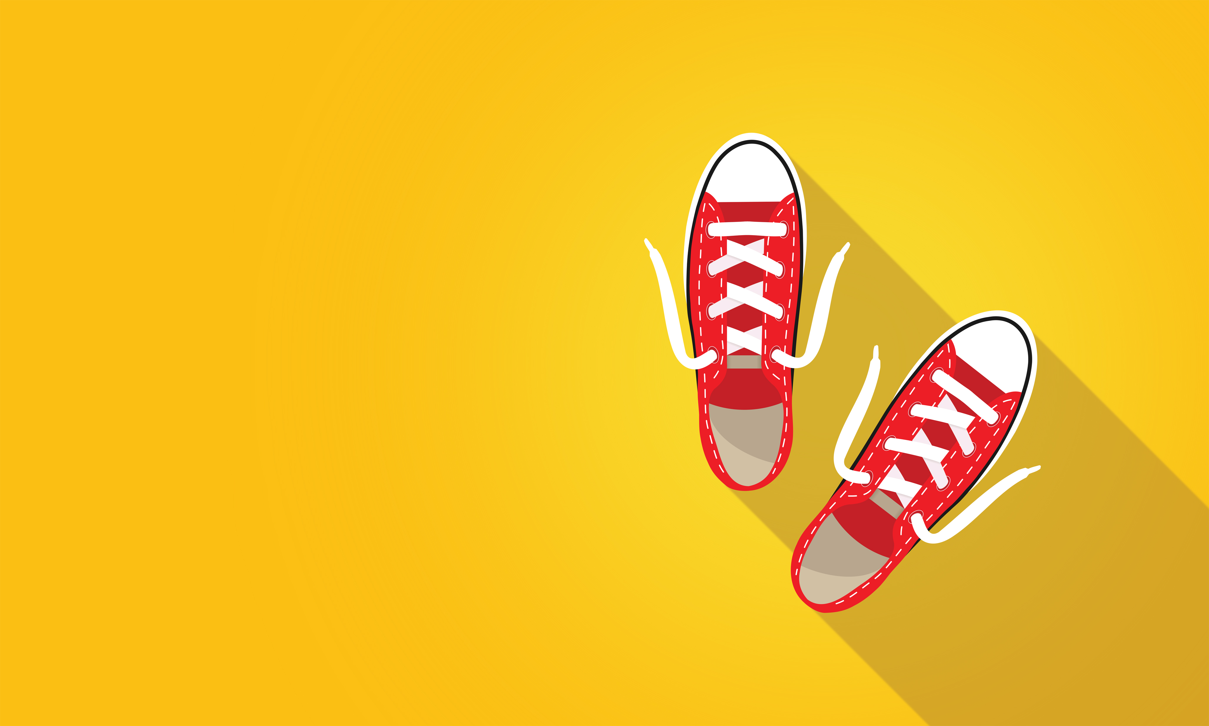 Red sneakers on bright yellow background photo
