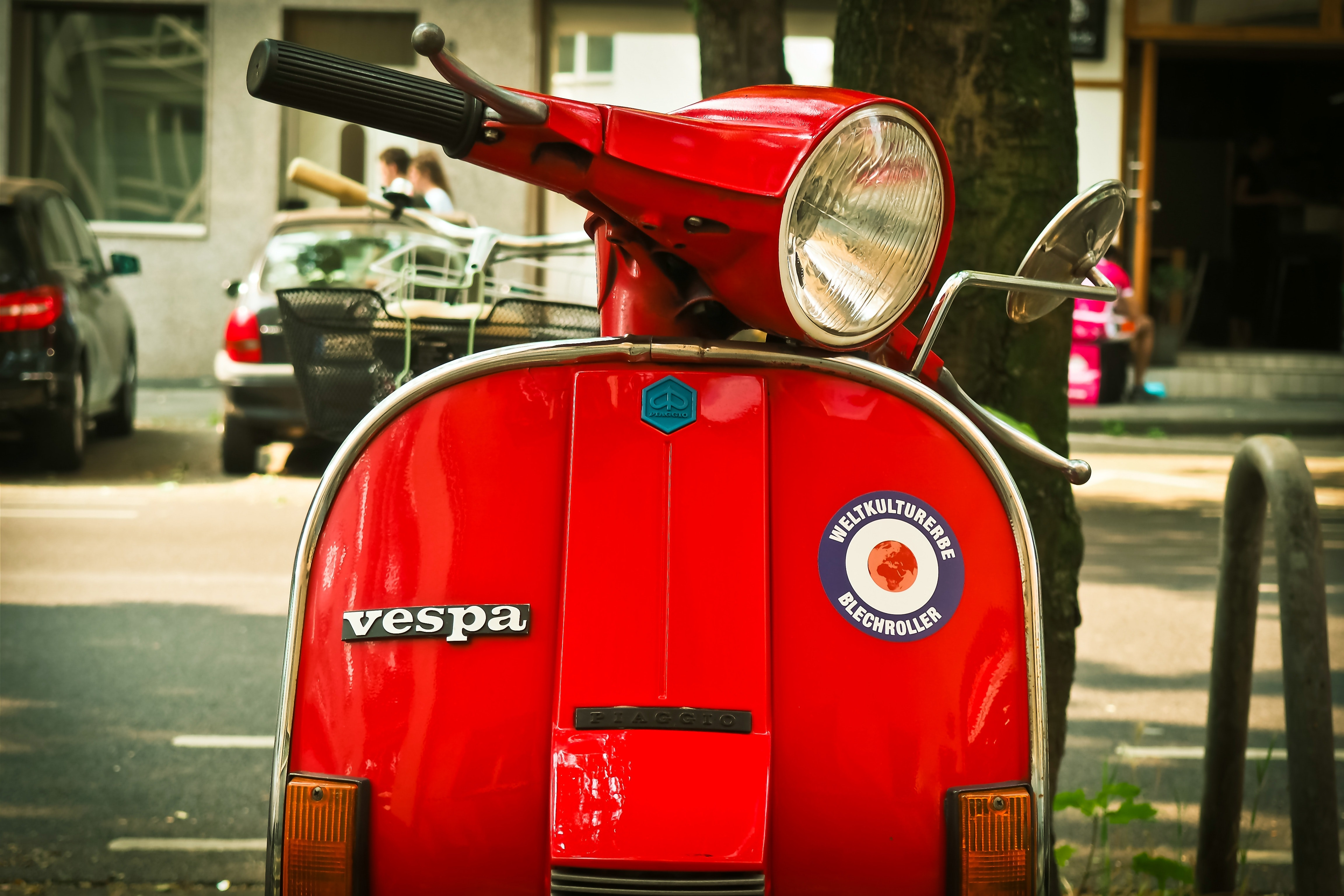 Red vespa motor scooter parked near tree during daytime photo
