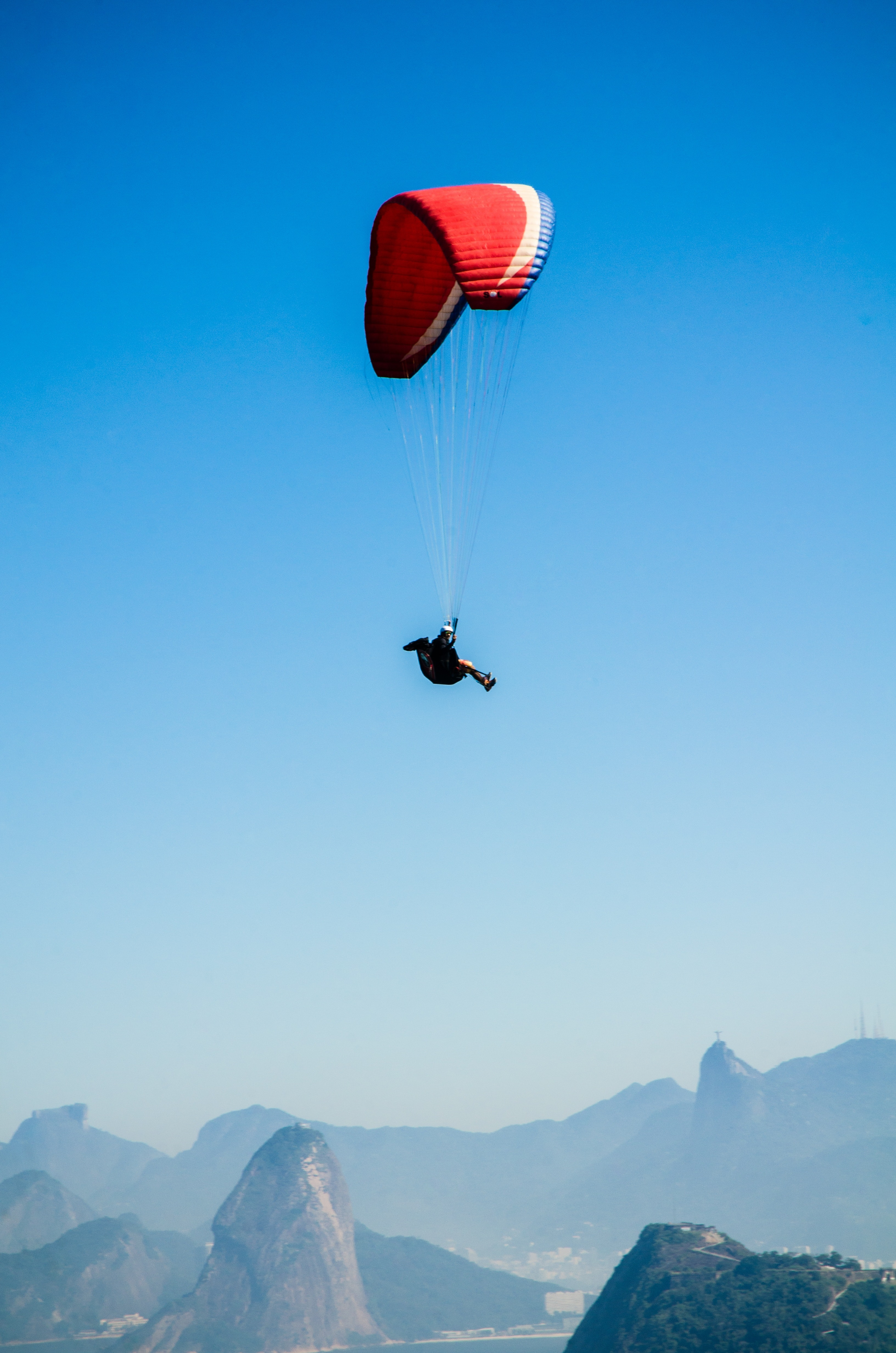 Red white parachute on top of mountains during daytime photo