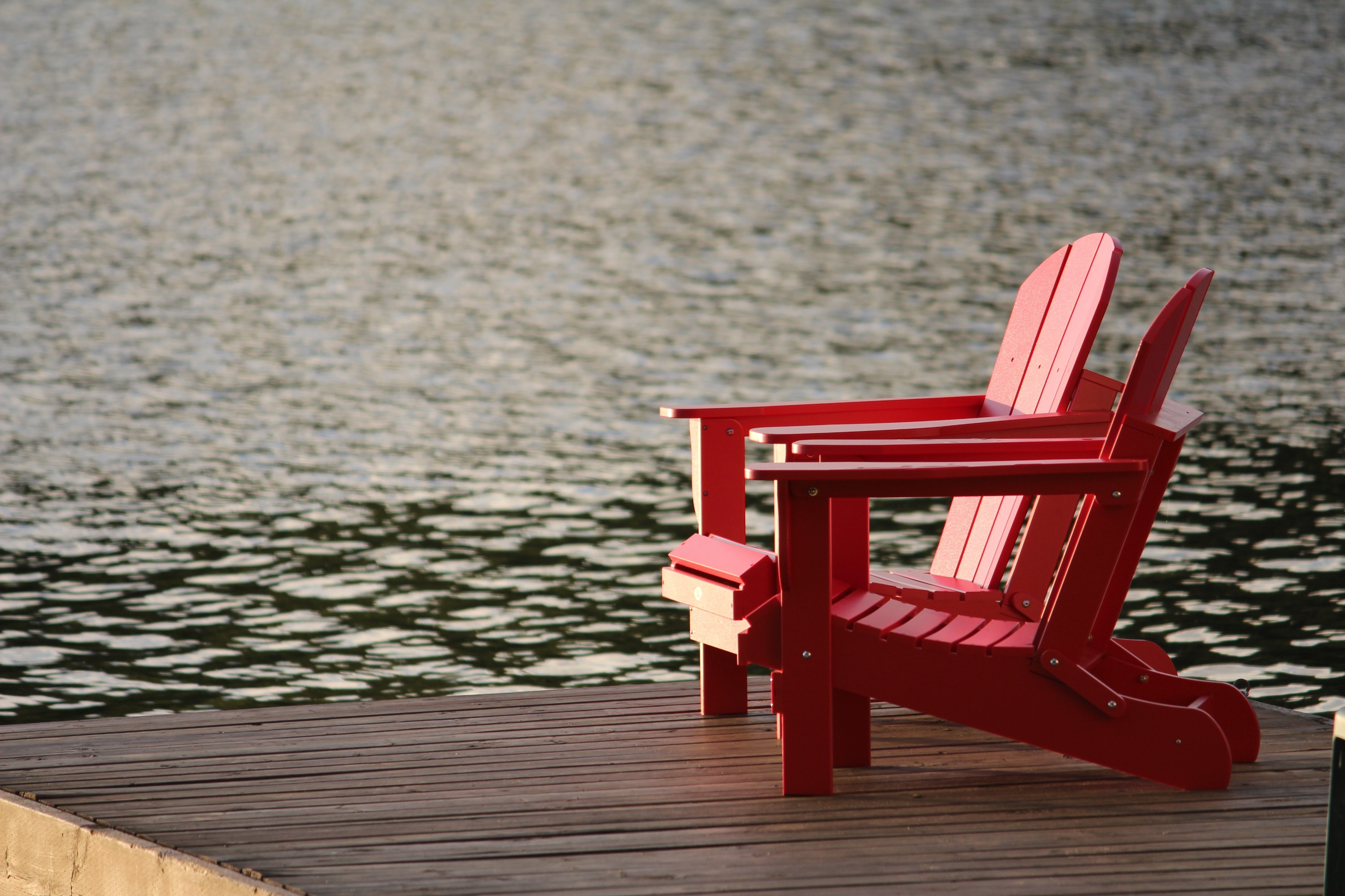 Red wooden lounge chair on brown boardwalk near body of water during daytime photo