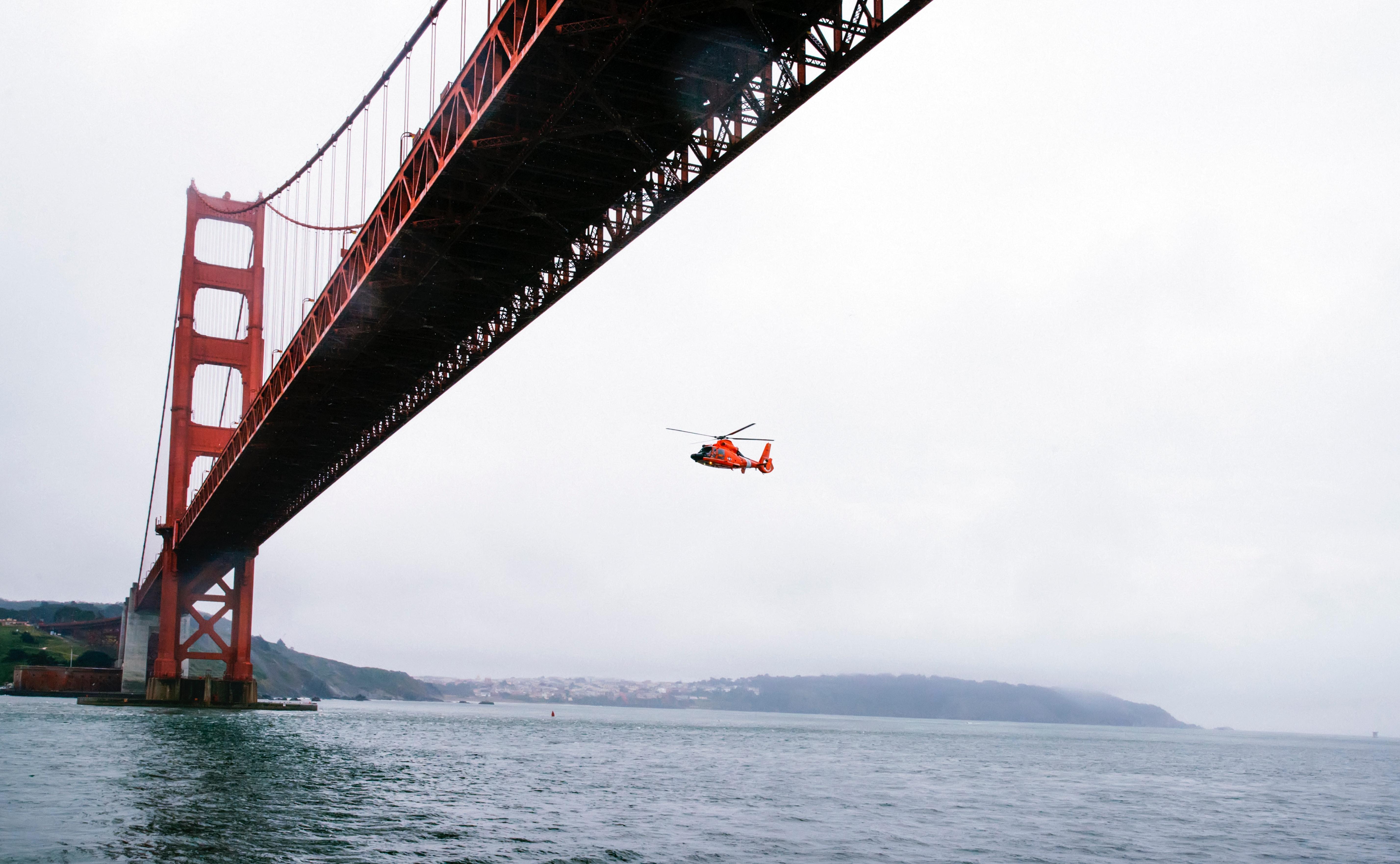 Rescue helicopter flying under golden gate bridge photo