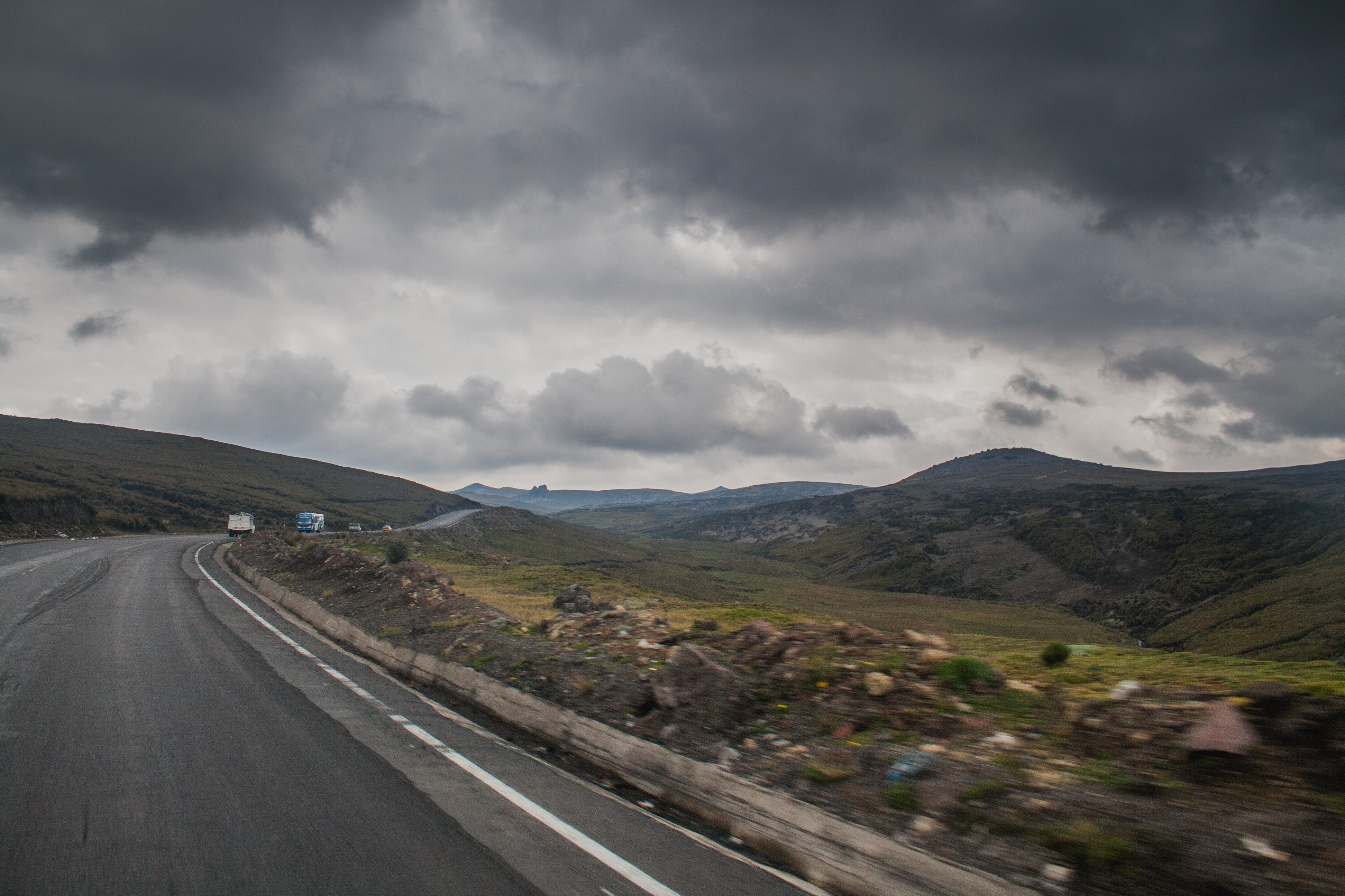 Road near brown stone during cloudy photo