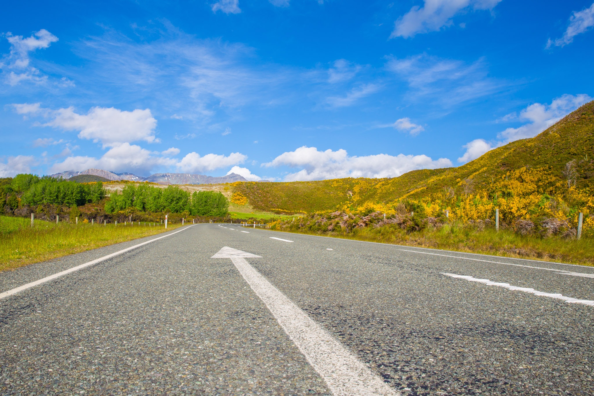 Road passing through landscape against blue sky photo