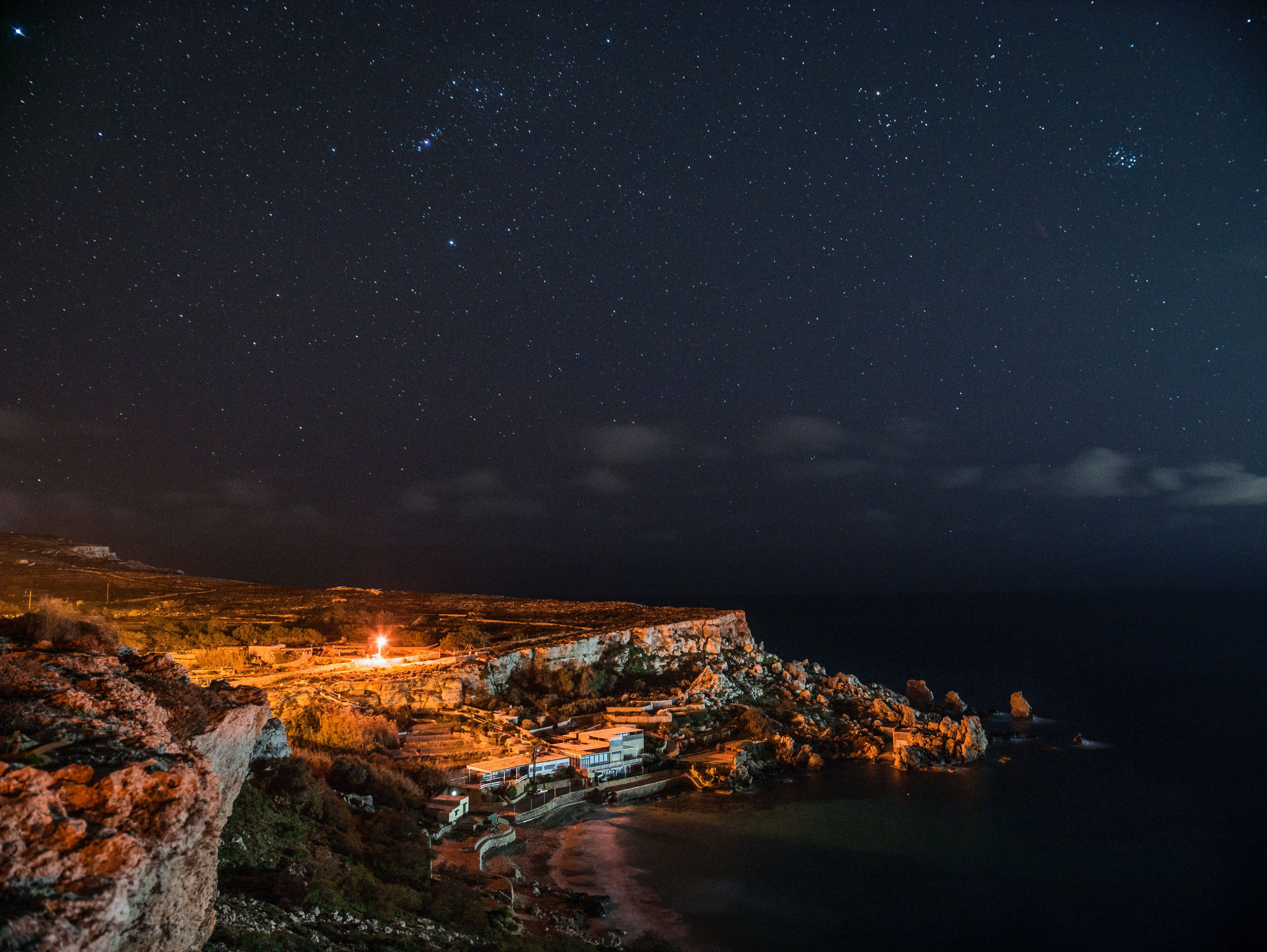 Rock cliff near body of water under clouds and sky during nighttime photo