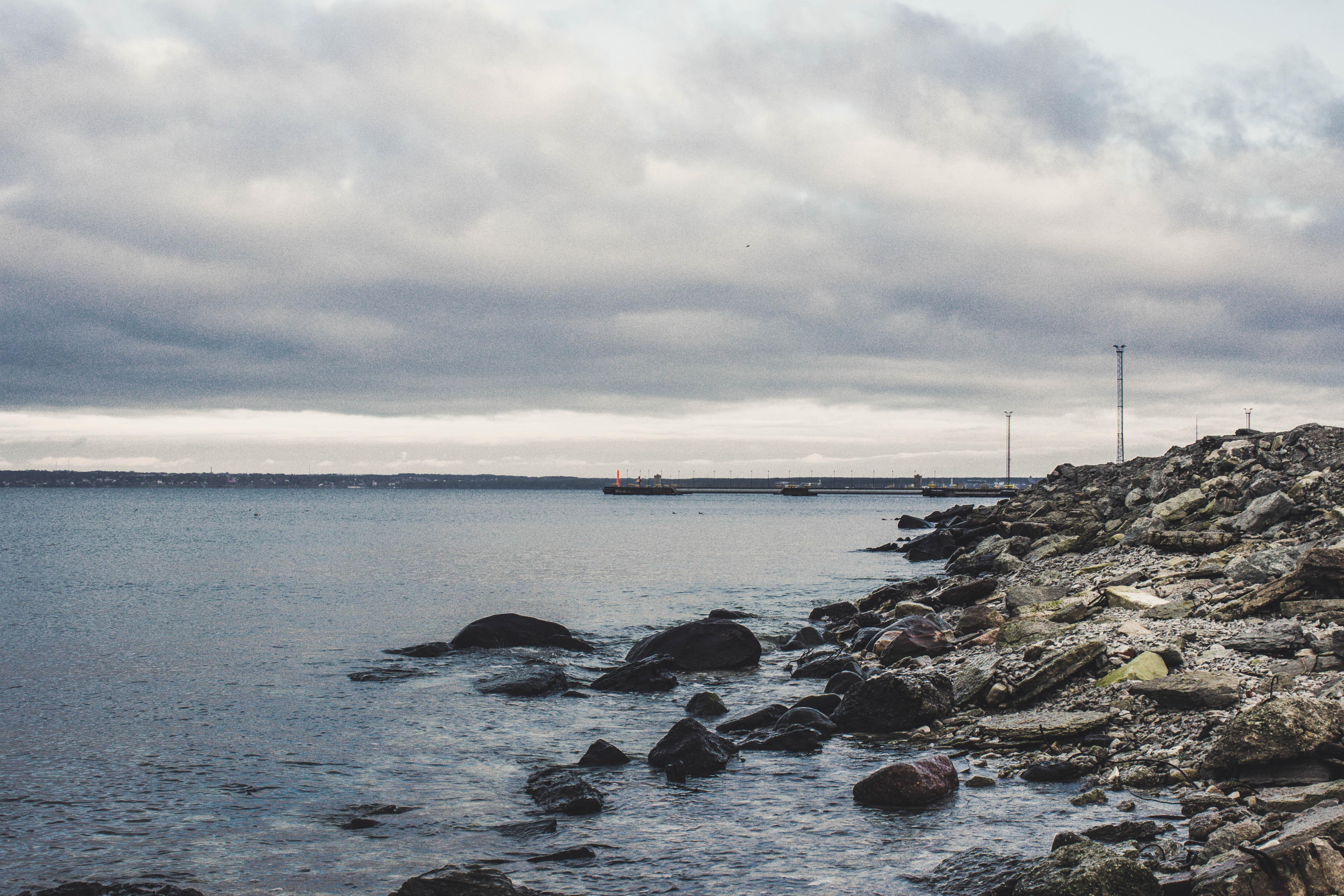 Rocks beneath the sea under cloudy sky photo