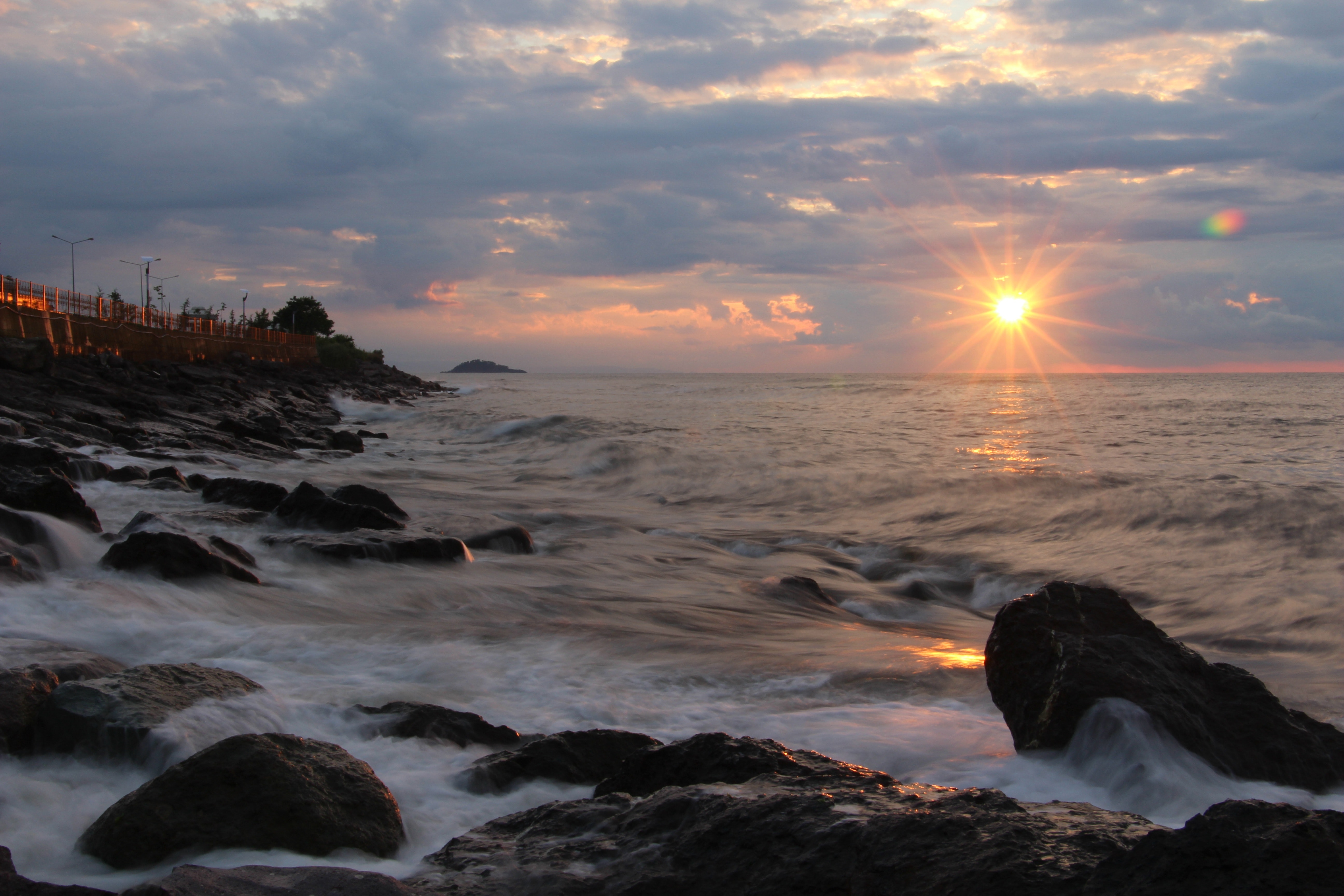 Rocks on seashore during sunset photo