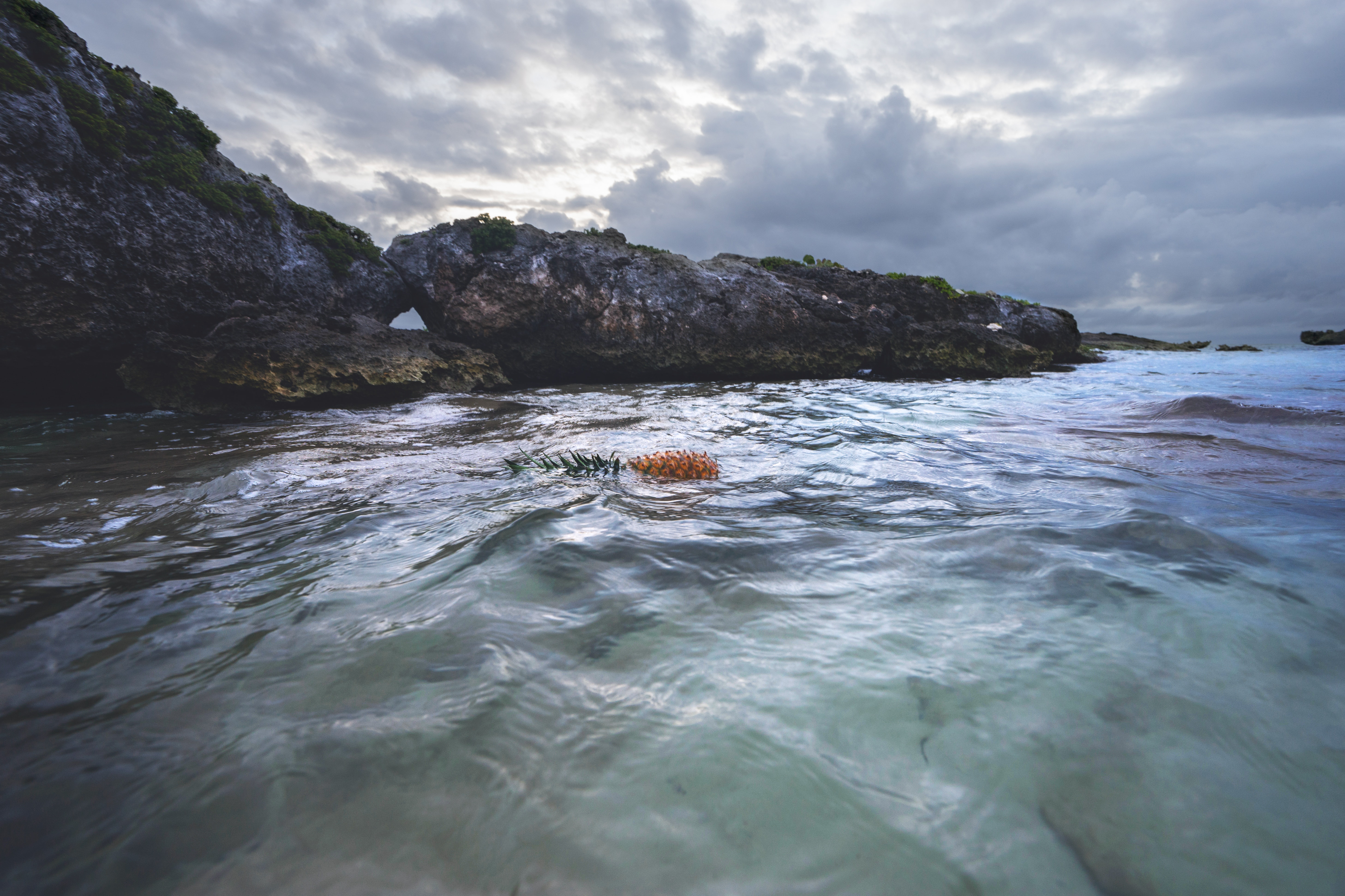 Rocky cliff near calm sea under gray cloudy sky photo